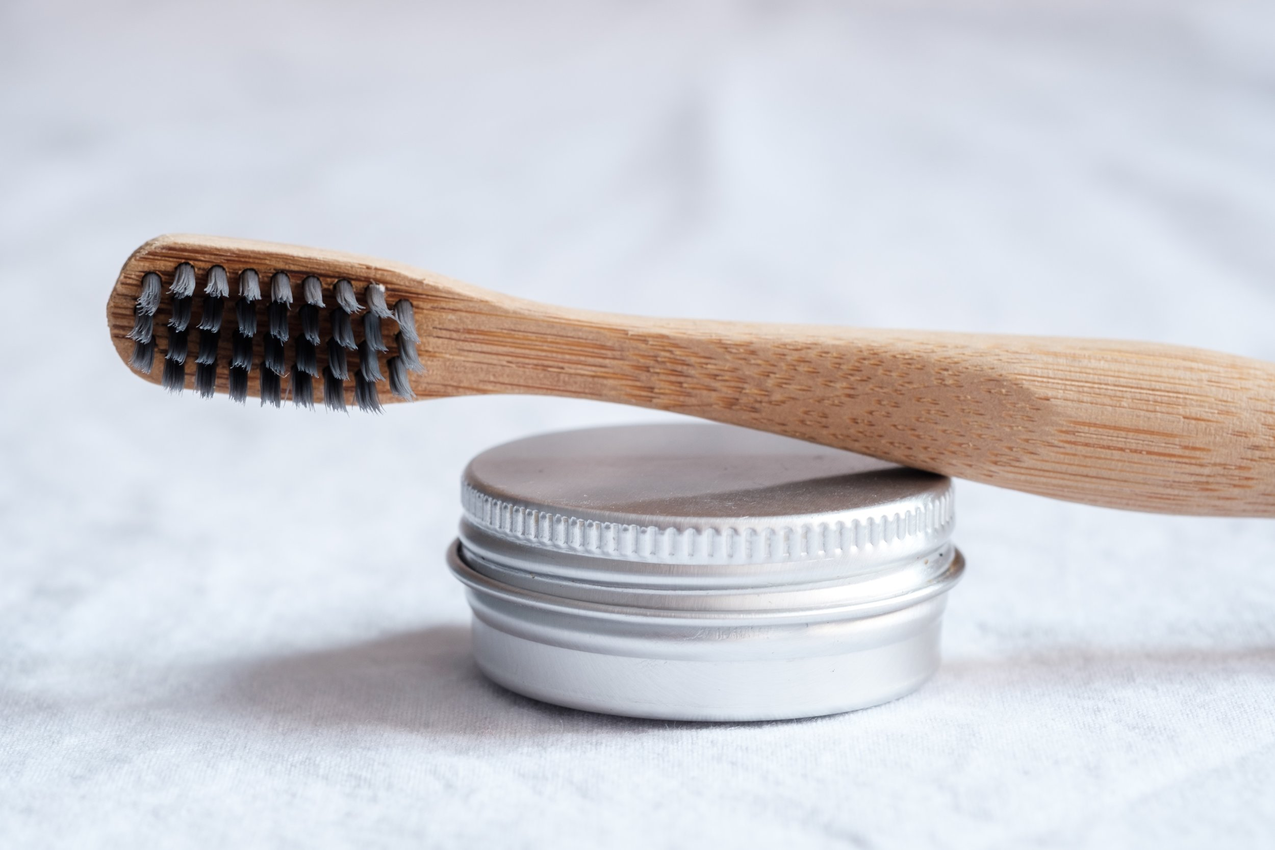 bamboo toothbrush on top of tin