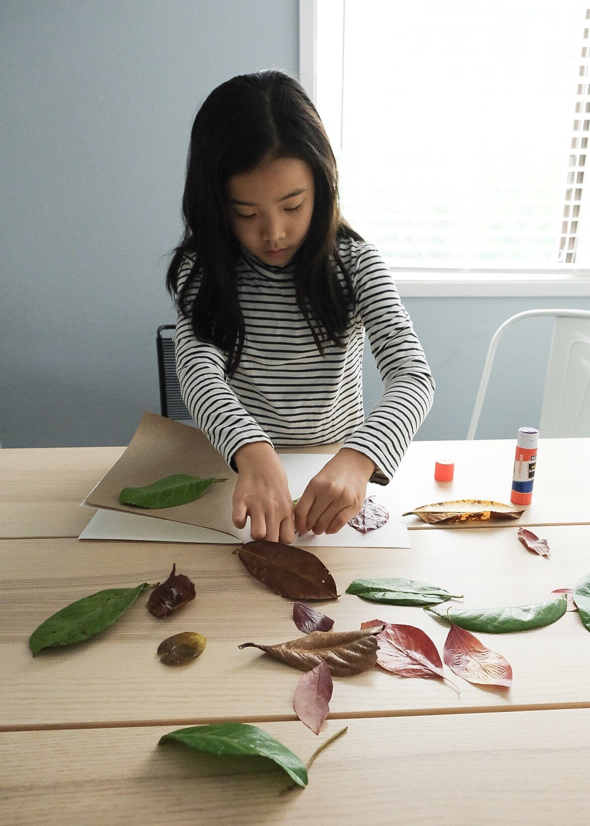 When the mod podge was dry, the girls arranged and glued the leaves in the book. For the book, we mixed heavyweight watercolor paper + brown kraft paper, folded them in half, and hand sewed them together along the folded line.