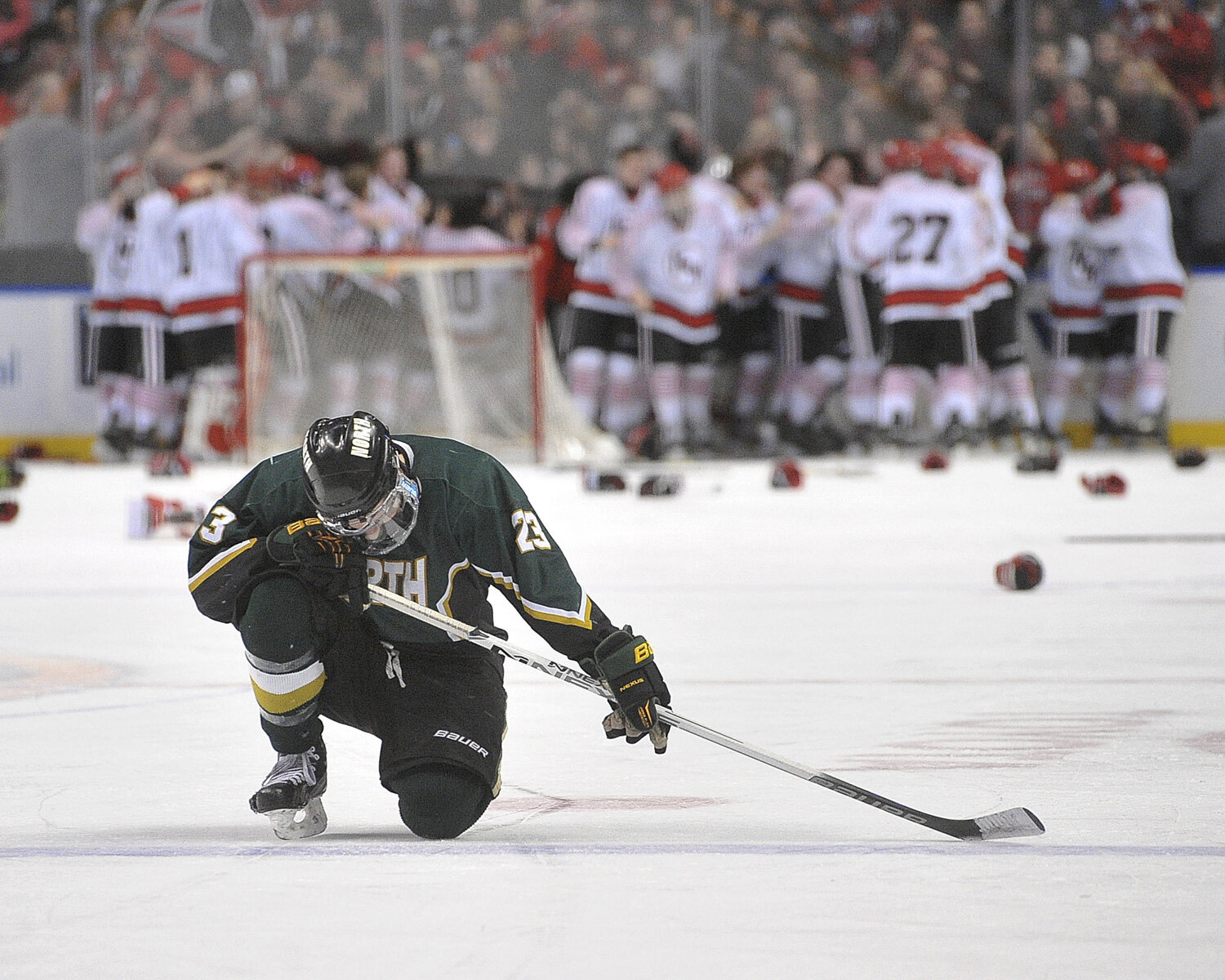 Spartans Brian Couto kneels in shock as Williamsville North falls to Niagara-Wheatfield 6-4 in Federation League finals at First Niagara Center.