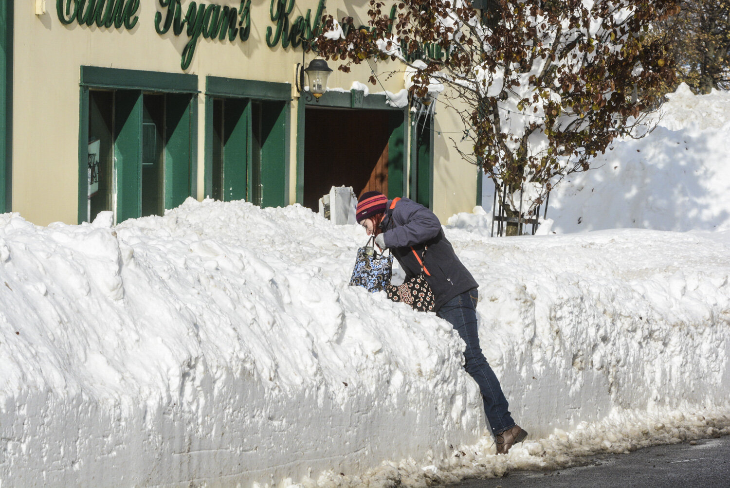 Jessica Ganska climbs over a four foot trench cut in Central Avenue, Lancaster, to get to work at Twin Village Music. Friday was the first reprieve from the relentless storm that battered the area for four days.