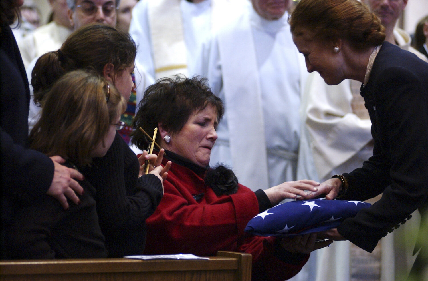 Jane Granville receives her son John's flag from Deputy Secretary of State, Henrietta Fore at the conclusion of John Granville's funeral at St. John Vianney Church in Orchard Park.  Granville, a Canisius High School graduate and South Buffalo native, was killed in the Sudanese capitol of Khartoum in 2008.