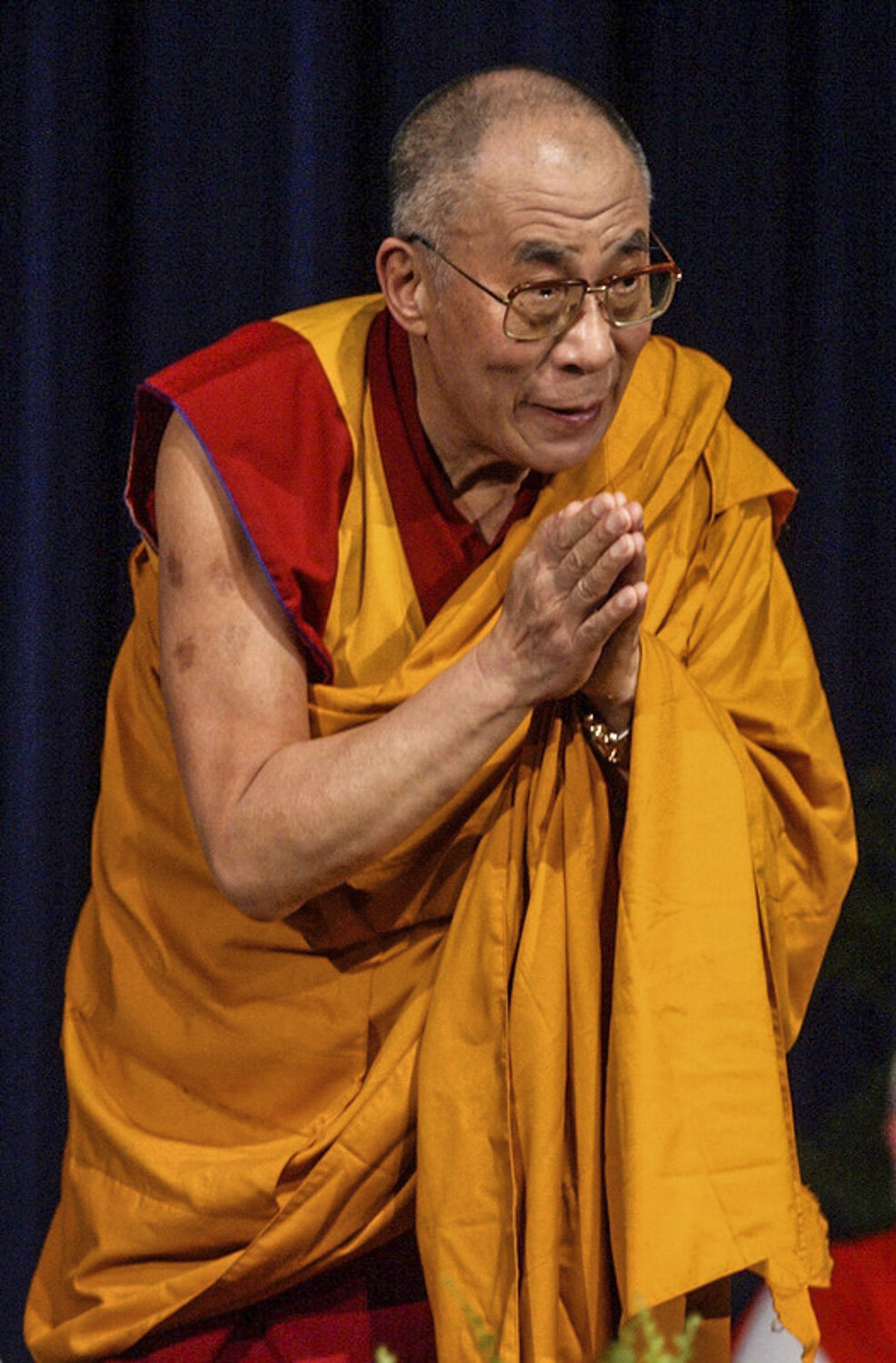 The Fourteeth Dalai Lama bows to the crowd as he makes his way to the podium during an interfaith service at University at Buffalo Alumni Arena.