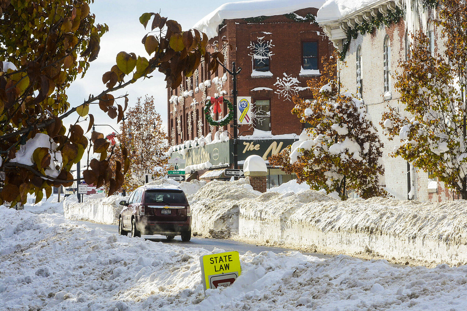 A trench four to five feet high is cut through Central Avenue in the Village of Lancaster. Friday is the first reprieve from the relentless storm that battered the area for four days.