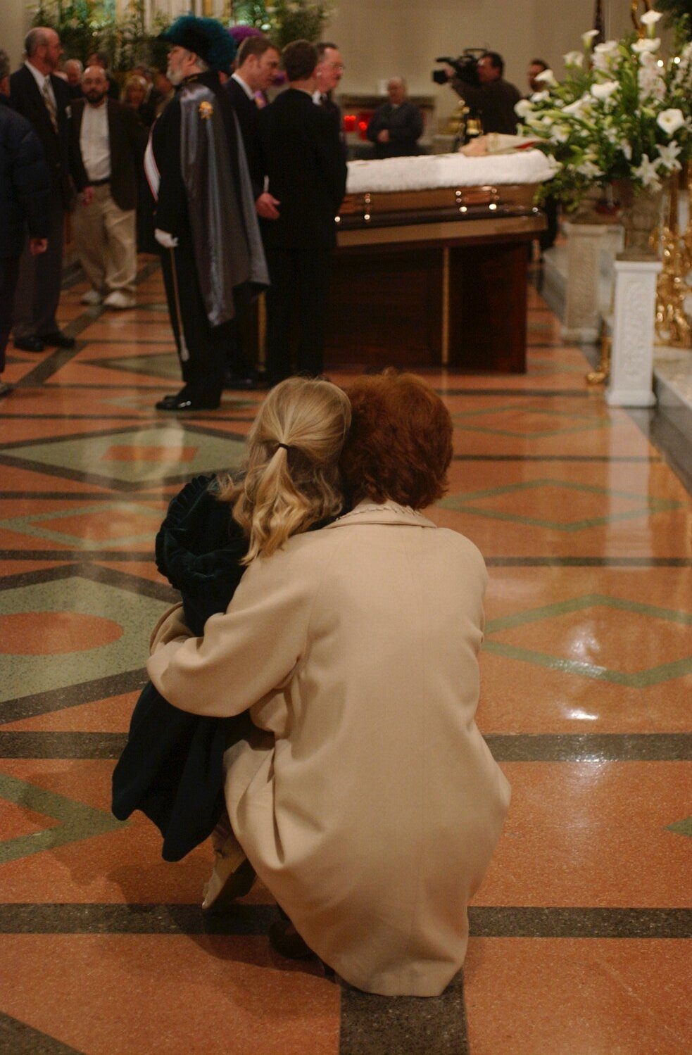 Colleen Burns kneels beside her daughter Reilly to say good by to Bishop Edward Head as his body lay in state at St. Joseph's Cathedral.  Bishop Head served the Diocese of Buffalo for 22 years. He died at 85.