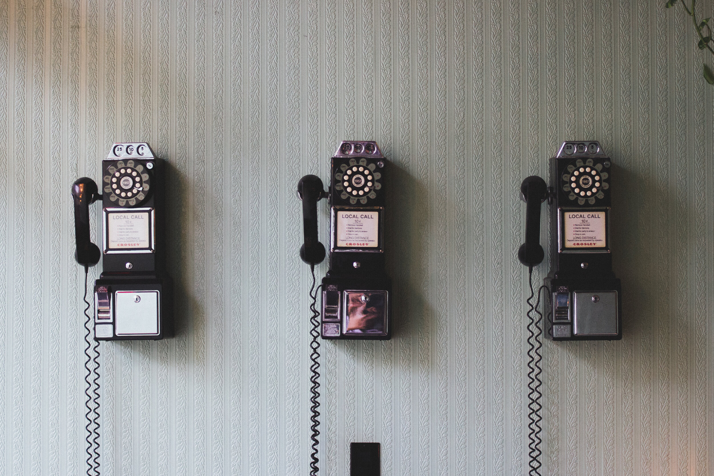 three old fashioned telephones on a striped wall