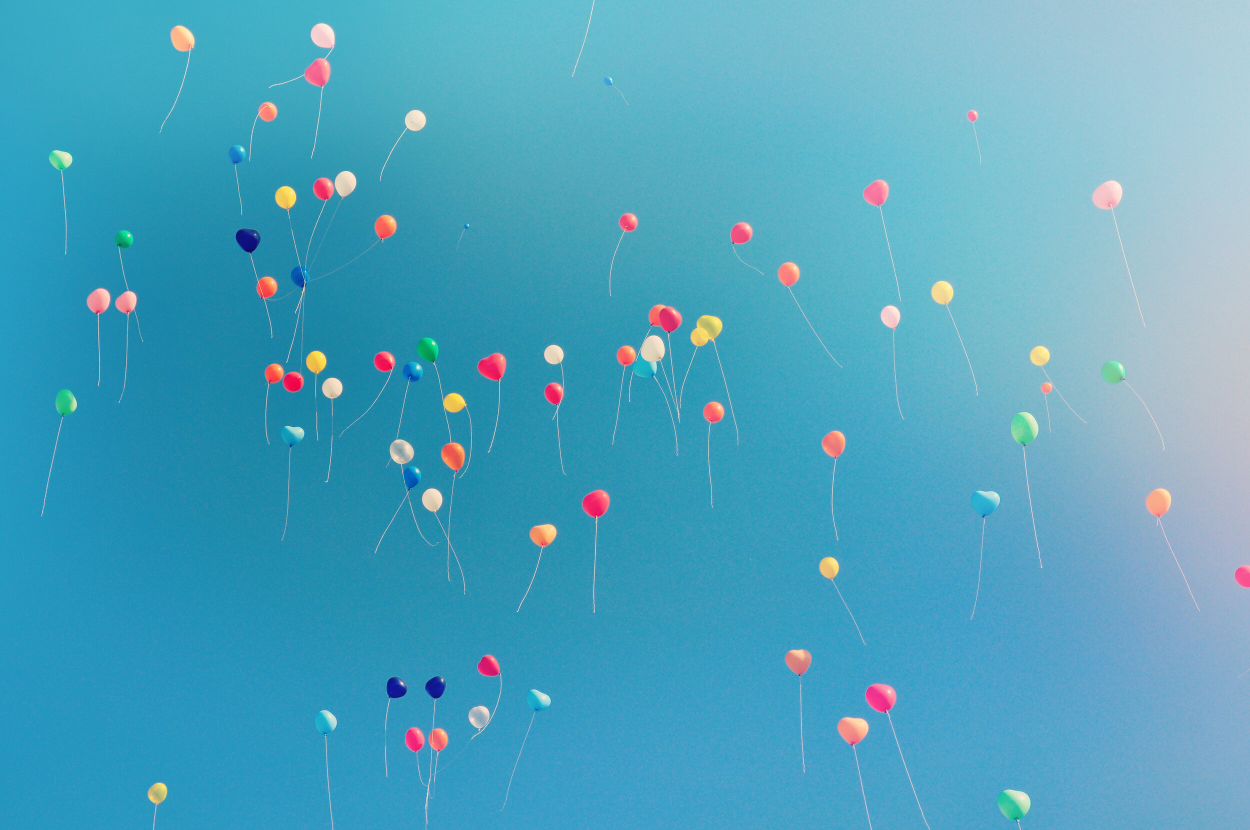 colorful balloons floating against a blue sky