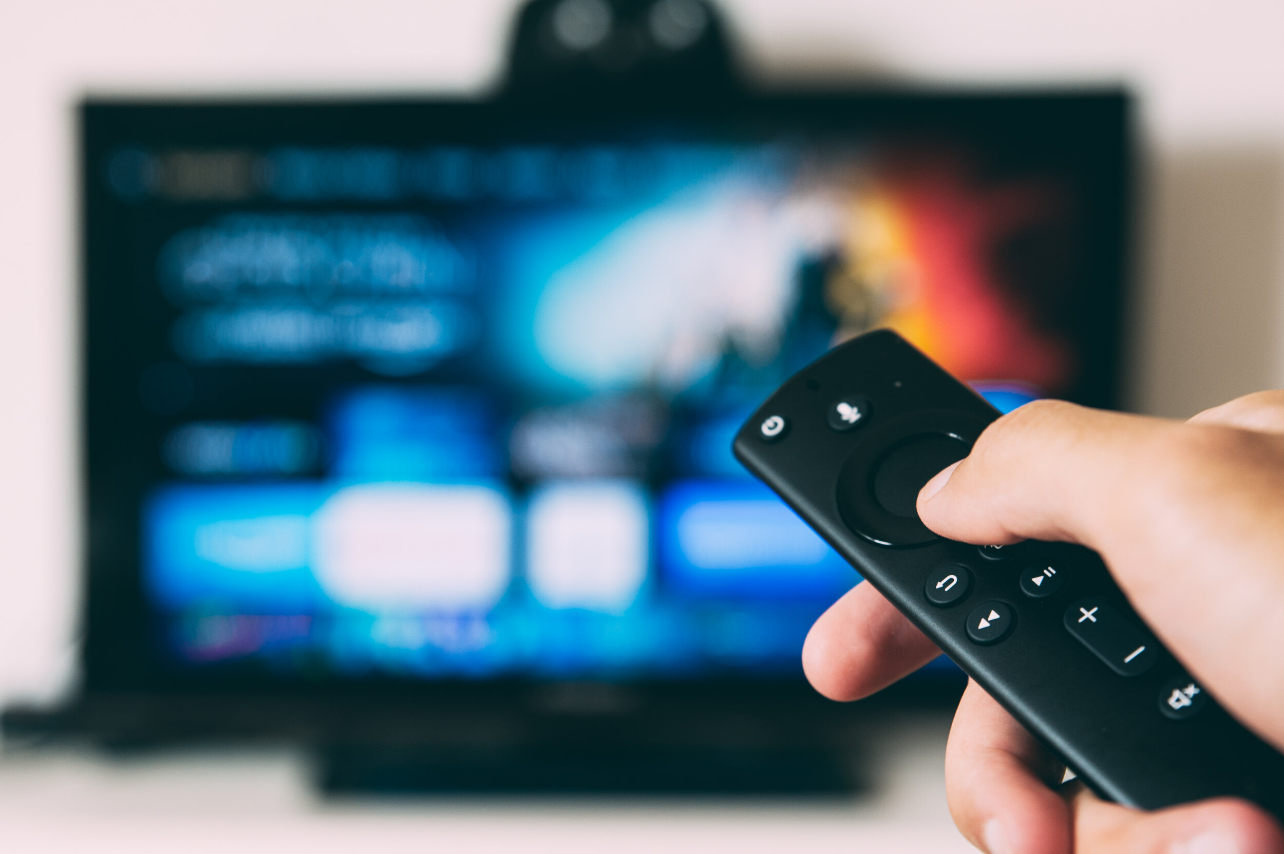 hand holding a remote in front of a blurred television