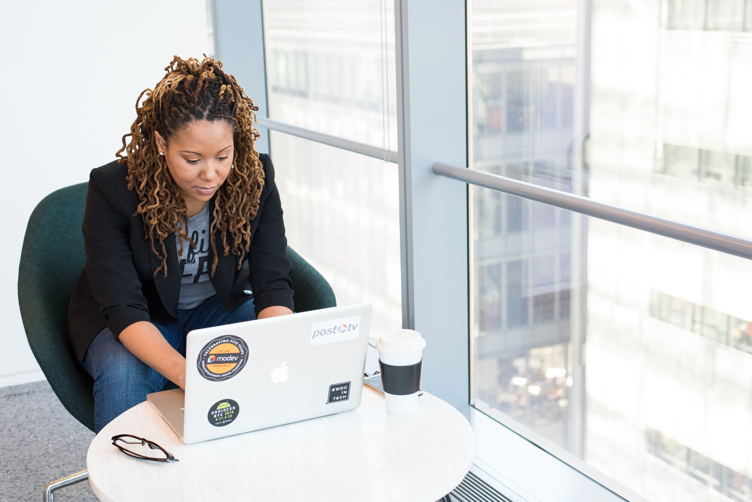 woman sitting at a coffee table in front of a laptop
