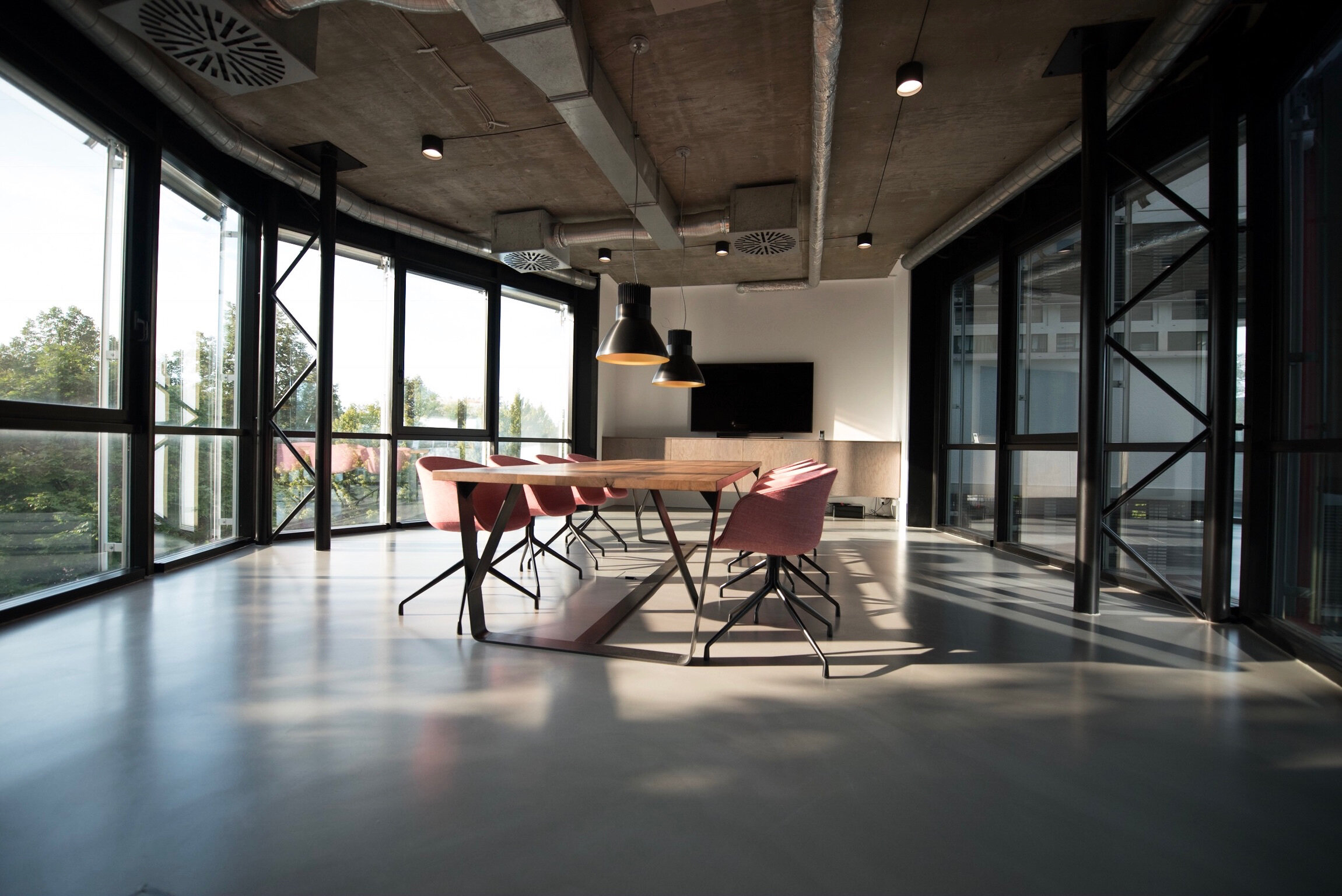 Industrial boardroom with lots of windows and pink chairs