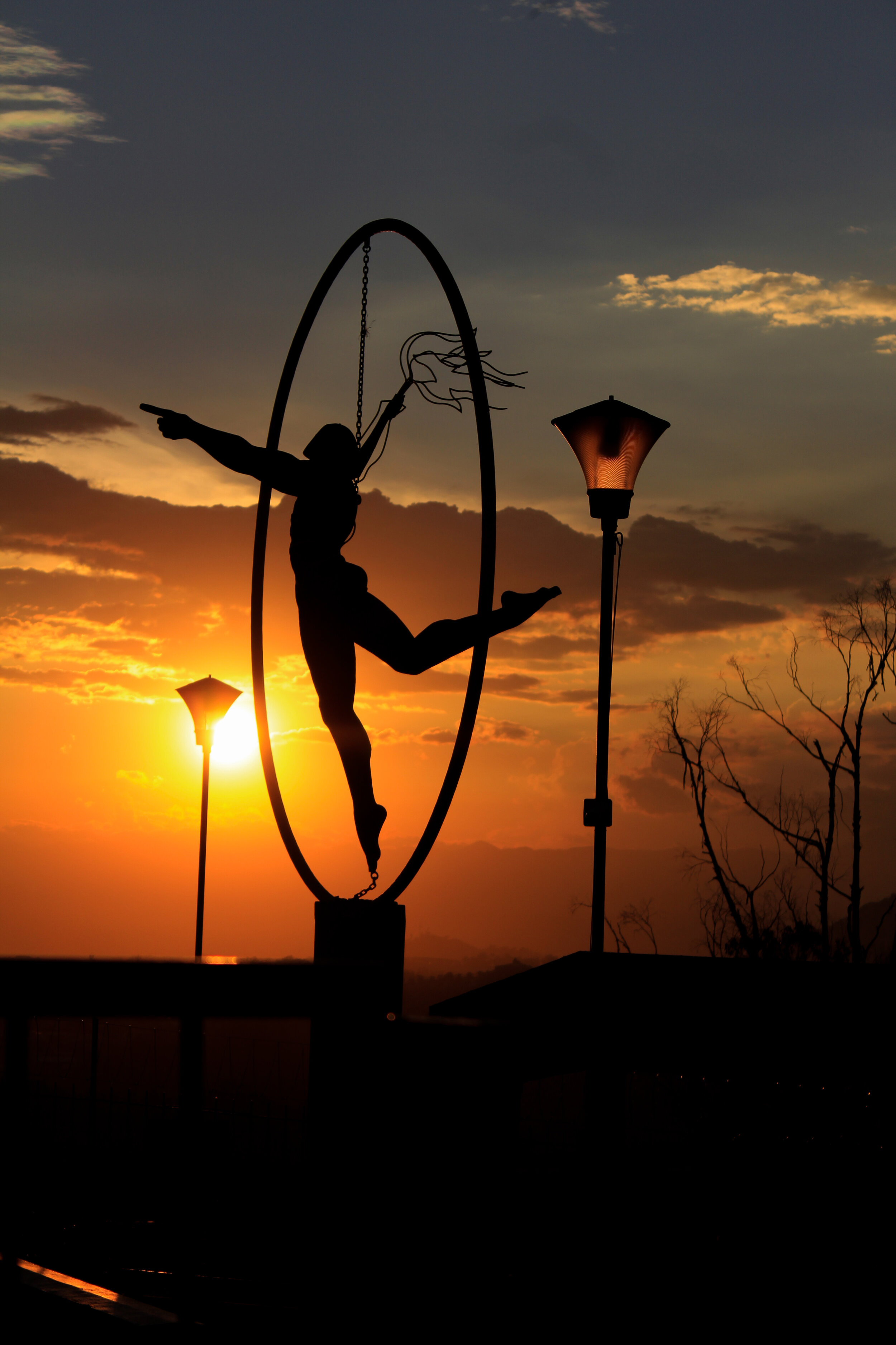 person inside a circle holding object in front of sunset