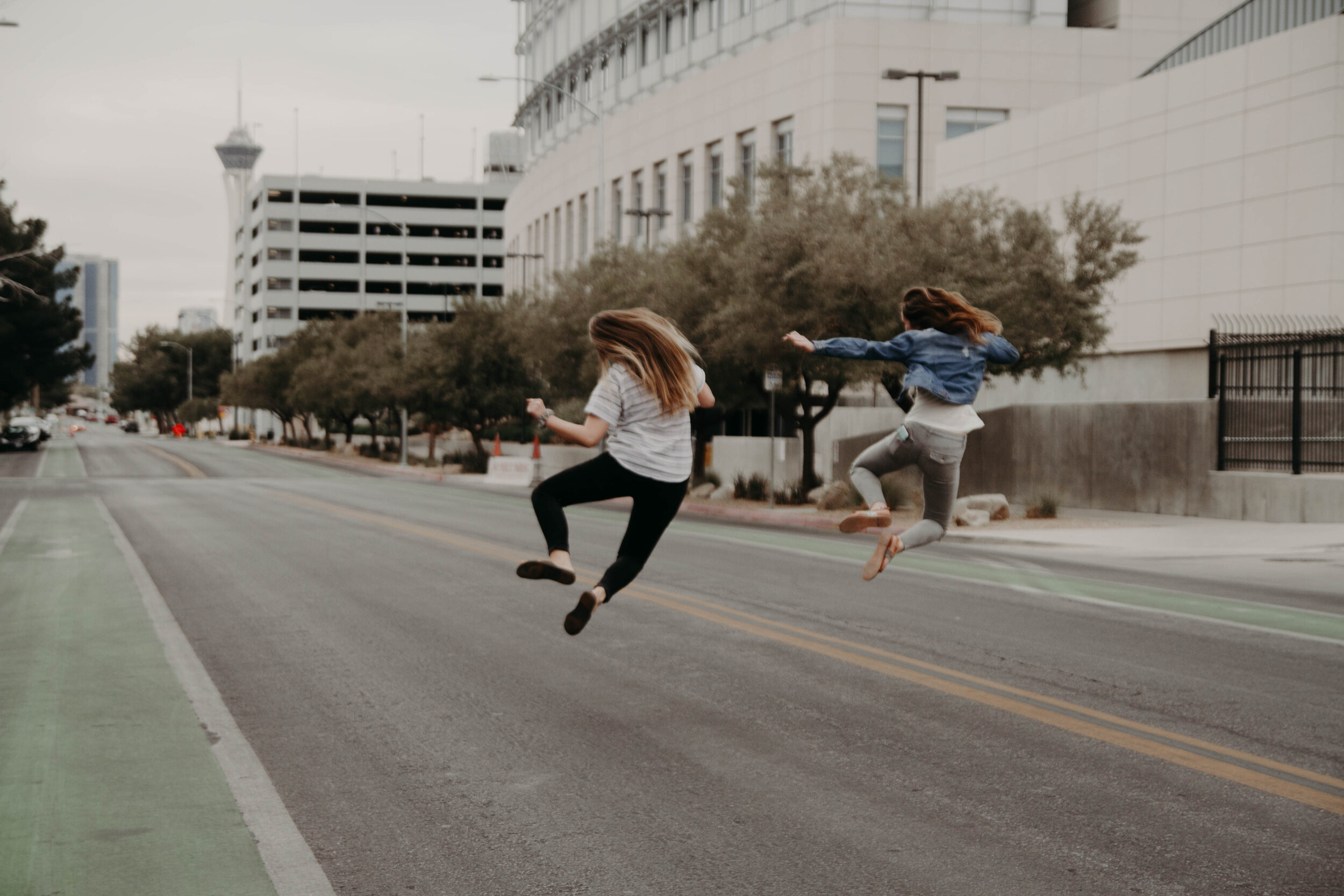 2 females jumping in the middle of a steet