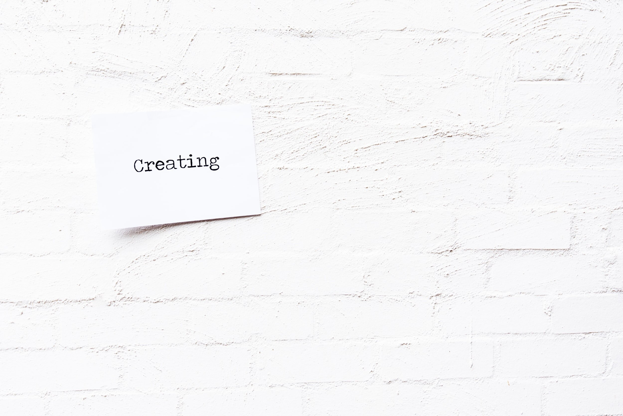 white paper with the word creating on it stuck to a white brick wall