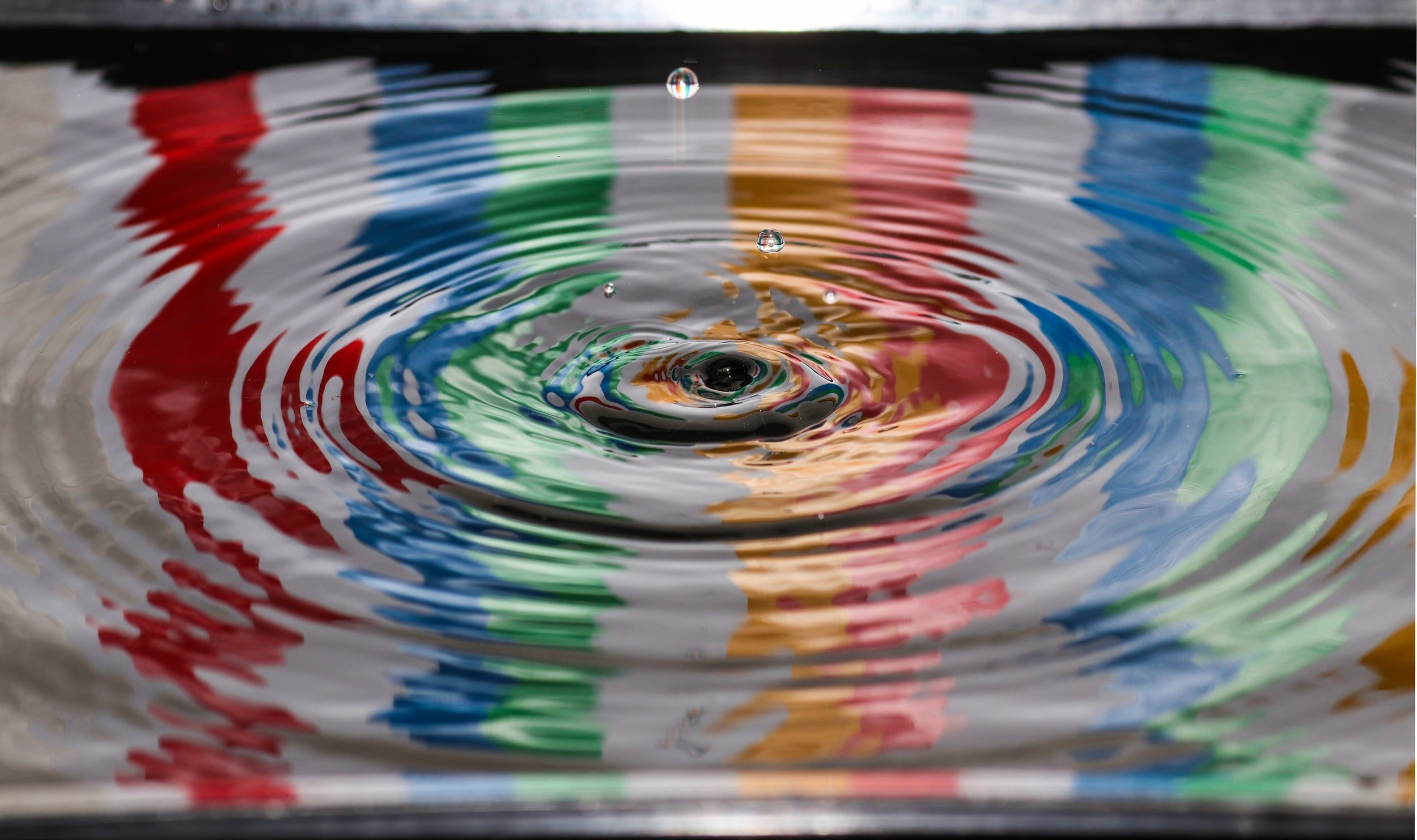 ripple effect of a drop of water on top of a puddle of water (reflection of colors)