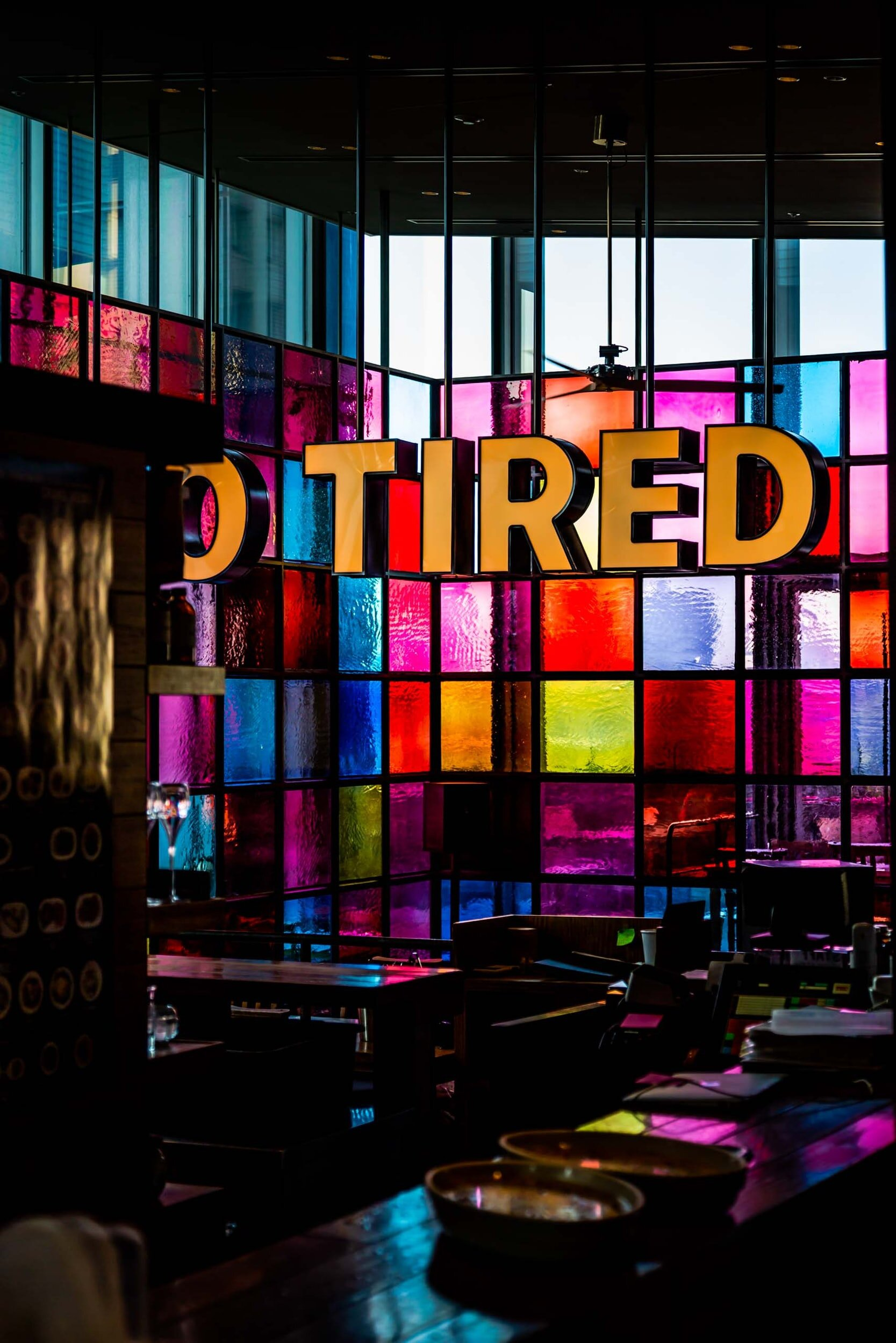 Tired sign in front of multi-colored glass