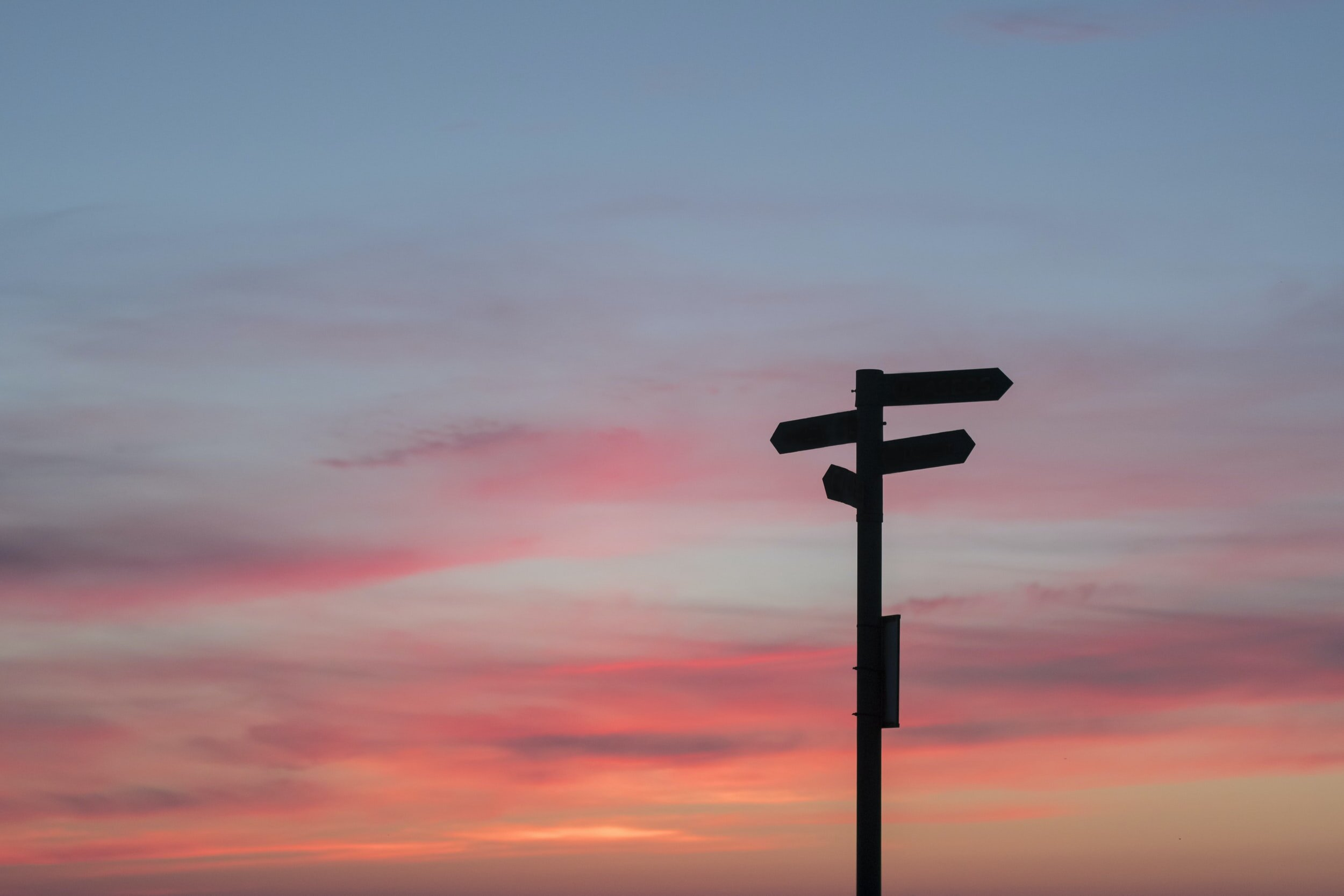 picture of a street sign in front a sunrise