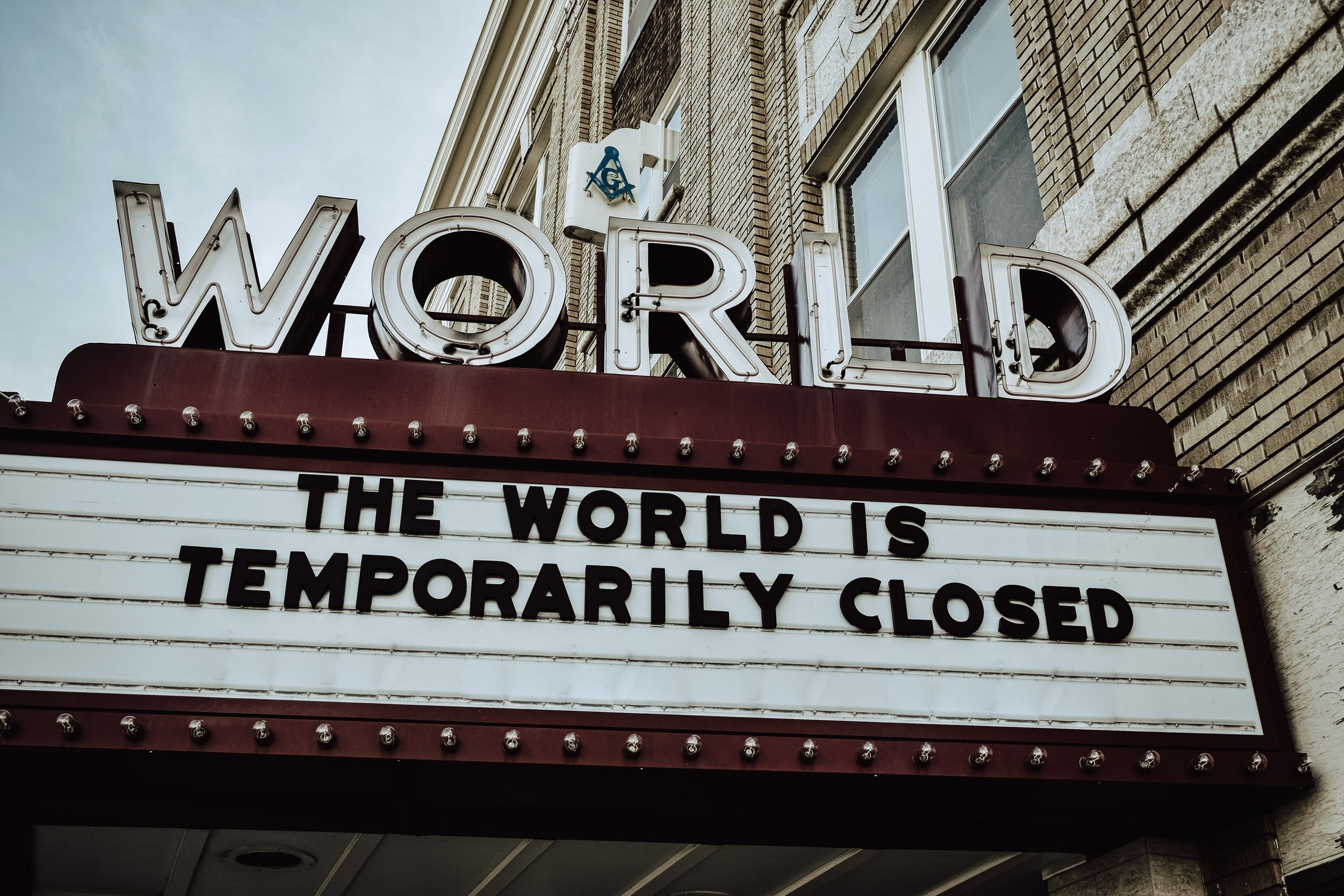 old movie theatre sign that reads, World: The World Is Temporarily Closed