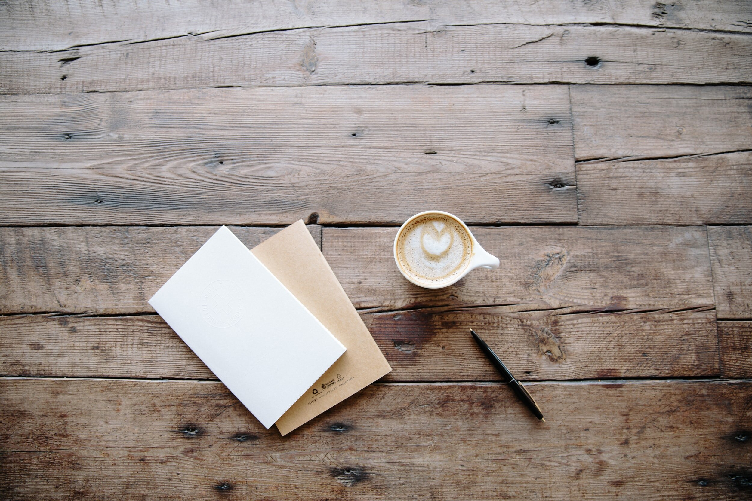 cup of coffee, pen a note pads on a wooden table