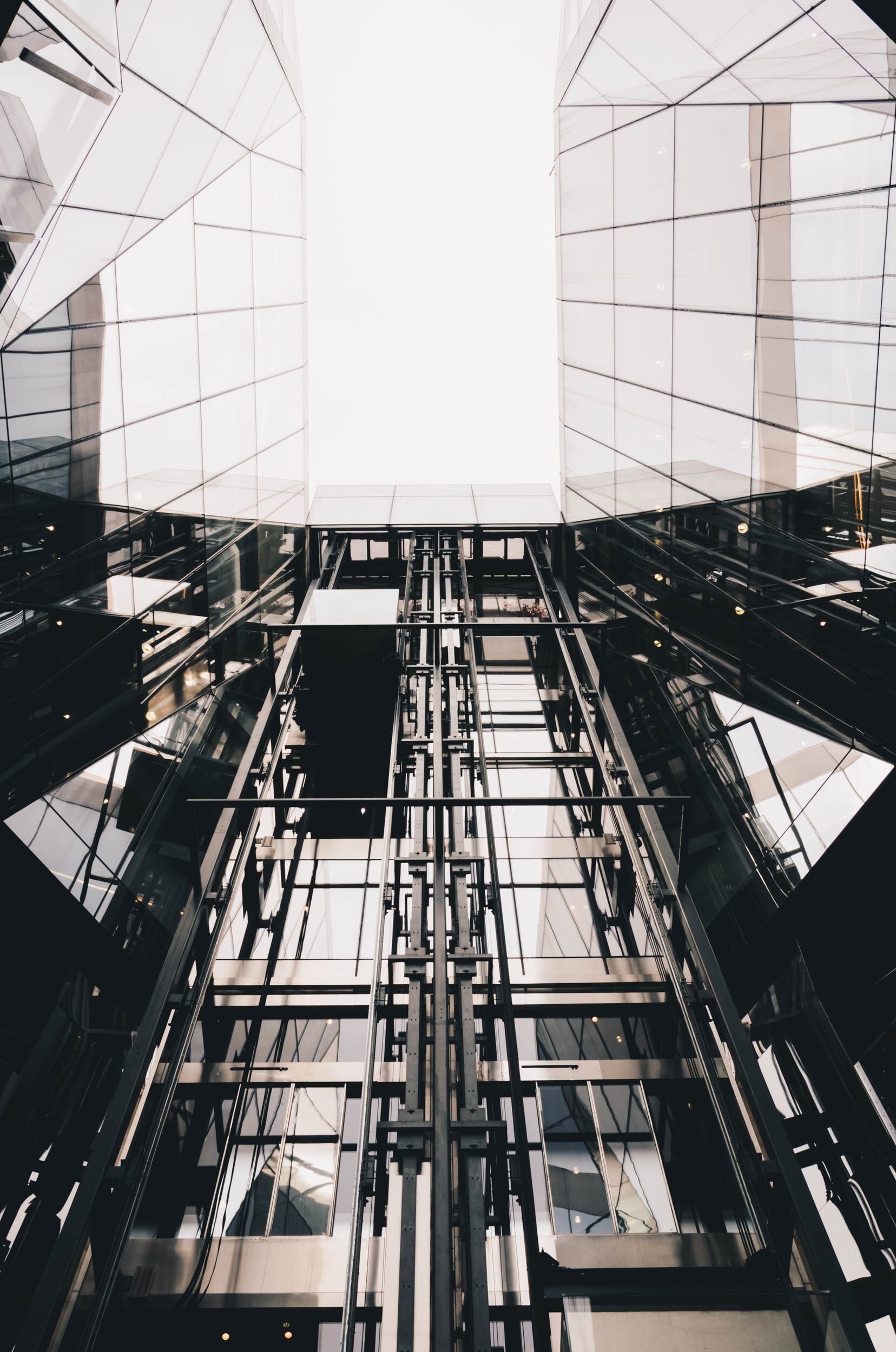 a picture looking up at tall glass buildings closer together outside