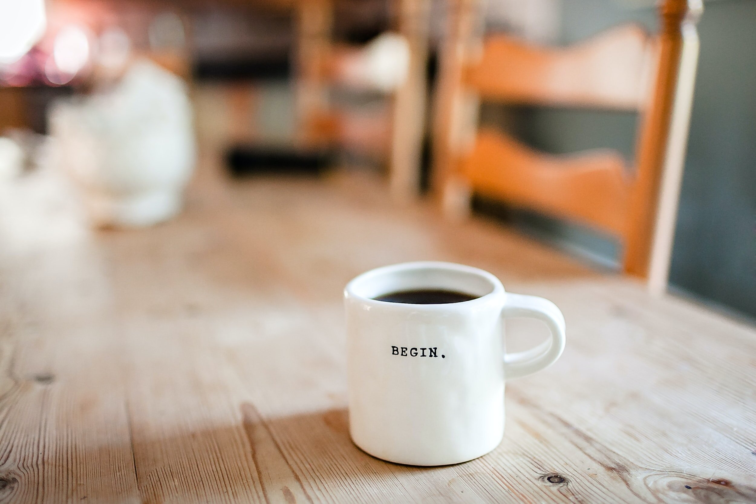 picture of a coffee mug on wooden table that reads BEGIN.