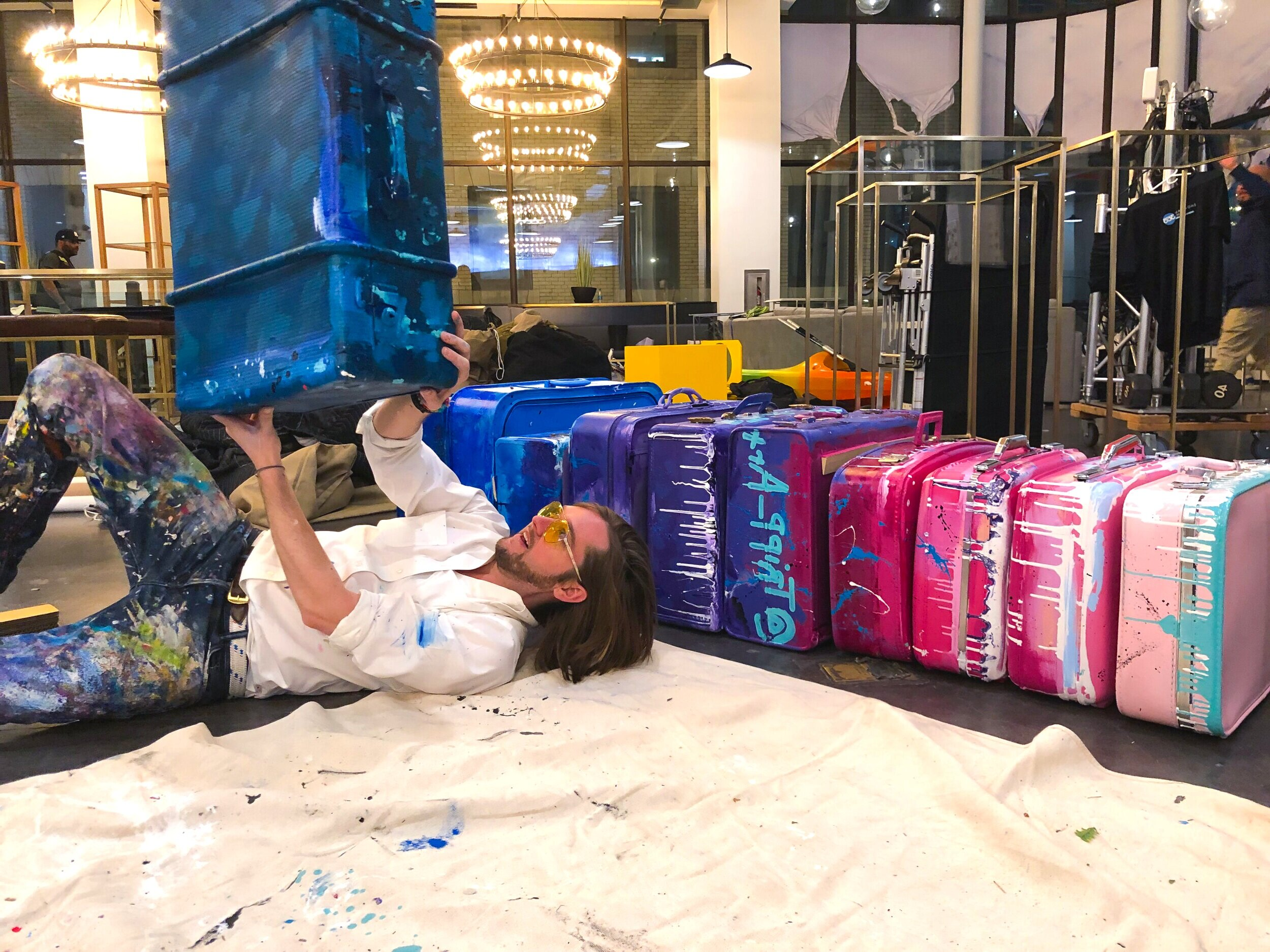 Mixed Media Installations - Whether it's a high end trade show or exclusive parties, Tripp creates engaging one-of-a-kind installations based on the theme or industry.  These provide not only entertainment for the guests, but also create opportunities to interact with the overall brand facing experience. Pictured: Tripp with custom painted suitcase installation for HRPR (Travel) trade show.