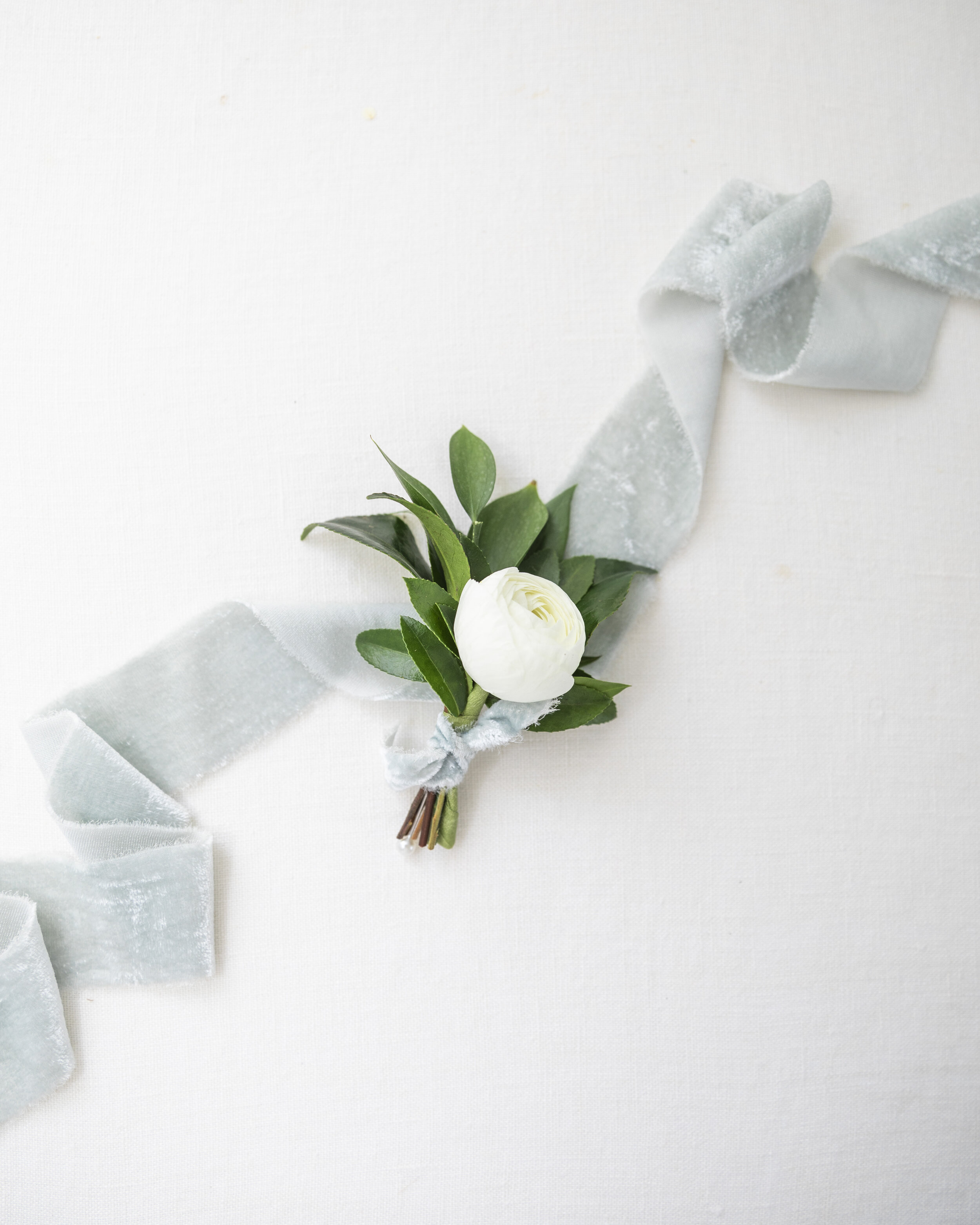 single white flower boutonniere boutonniere inspiration with greenery soft muted blue ribbon single boutinere pose inspiration floral tips and tricks for the utah provo bride bridal floral advise faux flower tips out of the box ideas cheap bouquet ideas professional provo utah florist#utahflorist #weddingplanning #claritylane #weddingbouquetinspiration #weddingflorals #softbrightlighting #provoutahflorist #provoutah #weddinginspo #provoweddingphotorapher