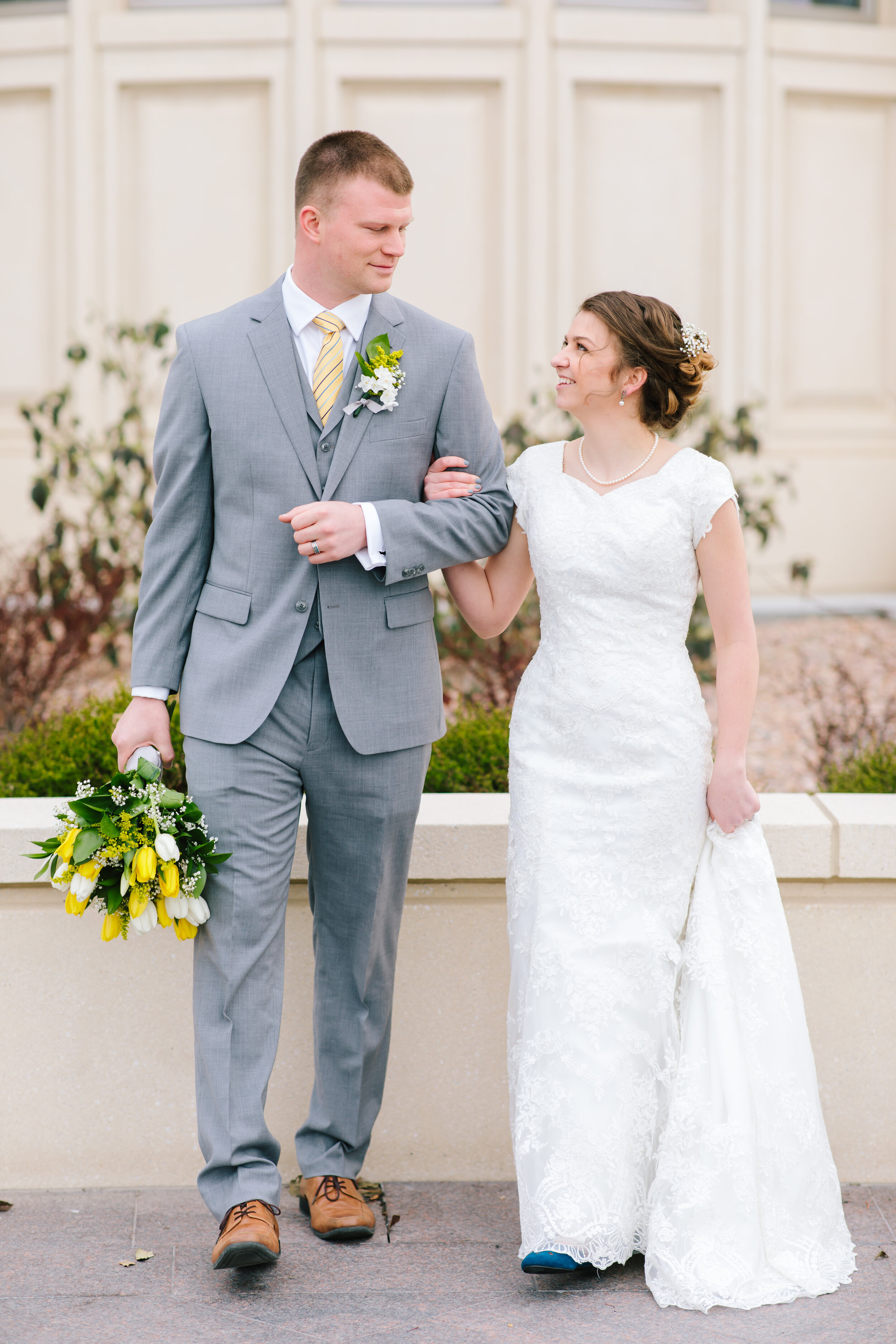 grey tux yellow and white florals payson temple grounds couple walking pose three piece tux groom outfit inspiration modest short tulip sleeved wedding dress wedding aesthetic inspiration couple goals temple grounds payson temple location wedding utah professional #eternalbuddies #weddingsession #weddinginspo #ldswedding #ldsbride #couplegoals #paysontemple #temple #profressionalphotographer #utah #love