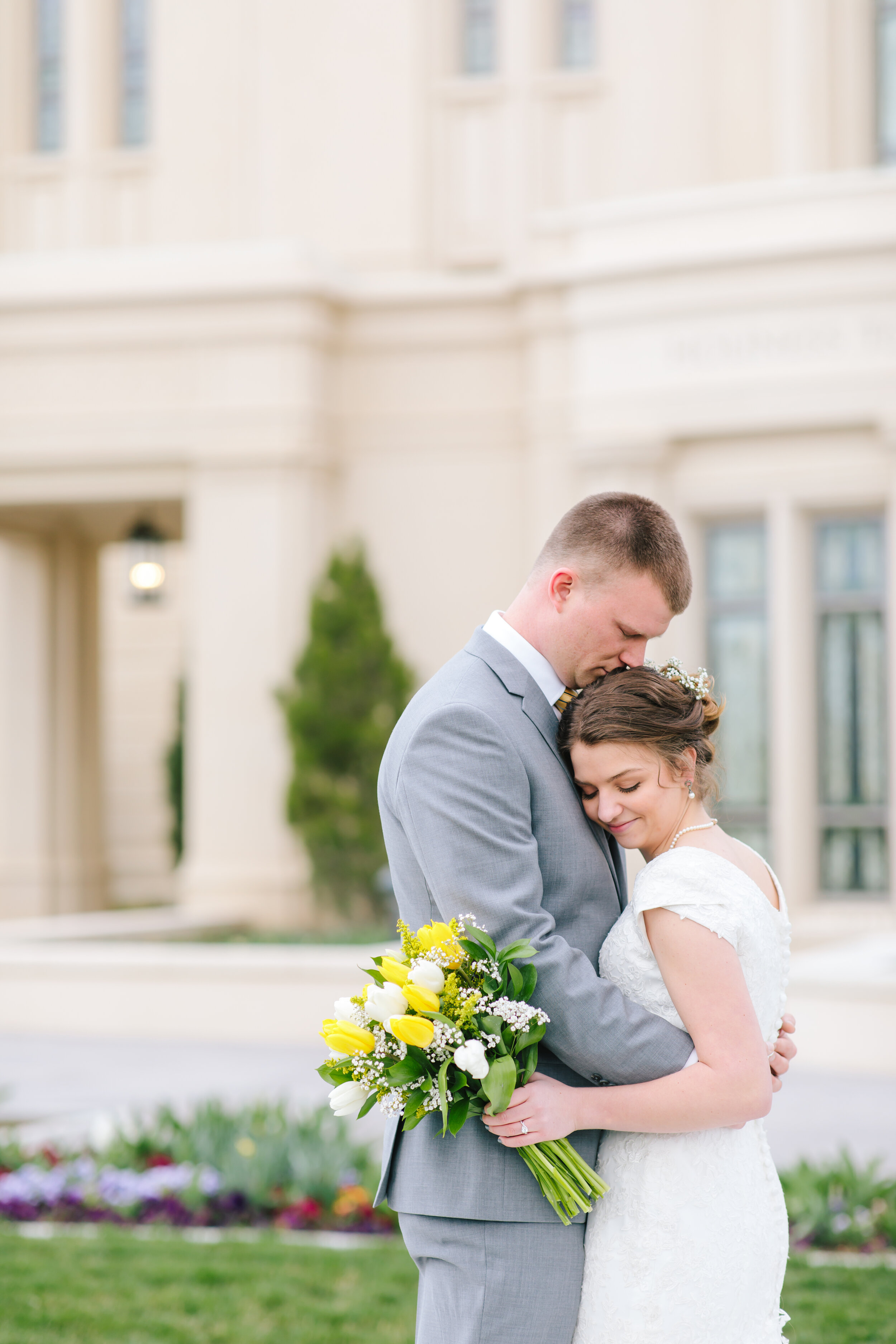 loving couple pose wedding hairstyle inspiration flowers in her hair wedding jewelry inspiration young love payson temple eternal marriages kissing head pose inspiration modest wedding dress back inspiration tulip sleeves lace dress lovebirds couple session #eternalbuddies #weddingsession #weddinginspo #ldswedding #ldsbride #couplegoals #paysontemple #temple #profressionalphotographer #utah #love