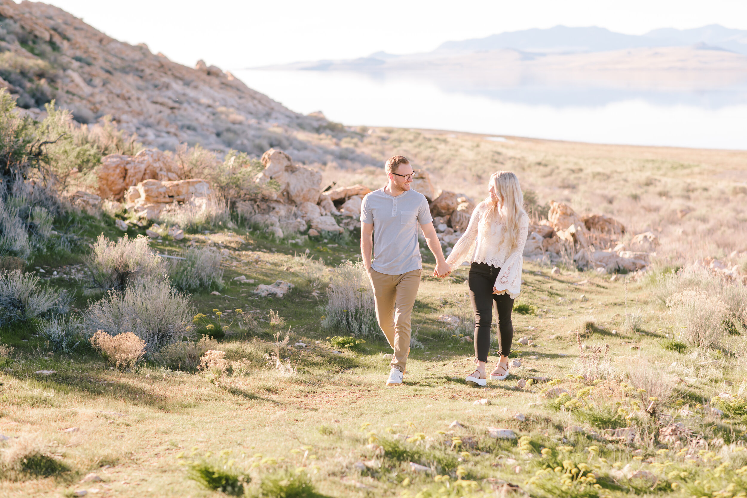 utah couple engagement photos close up dancing romantic flirtatious leading the way beautiful location antelope island casual semi formal outfit inspiration couple goals outside natural holding hands pose beautiful bright lighting glowing couple engagement ideas #antelopeisland #couplekissing #engagementoutfitinspo #locationinspo #romantic #outside #engagementposes #engagementideas #weddingring