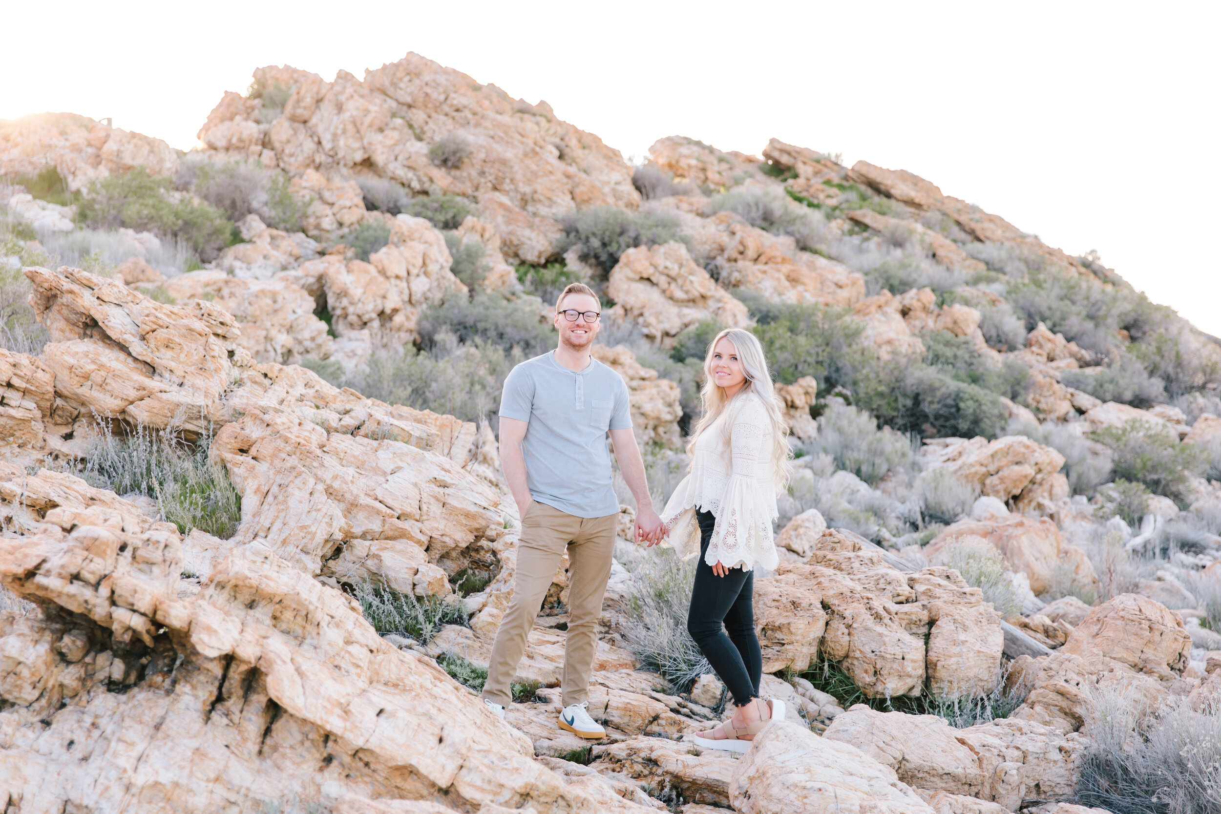 side of rock formation couple holding hands pose casual natural relaxed pose ideas #couplegoals #engagements rock formation location ideas antelope island utah rustic outdoor engagement ideas utah photographer clarity lane utah engagements serious pose goals in nature #antelopeisland #couplekissing #engagementoutfitinspo #locationinspo #romantic #outside #engagementposes #engagementideas #weddingring