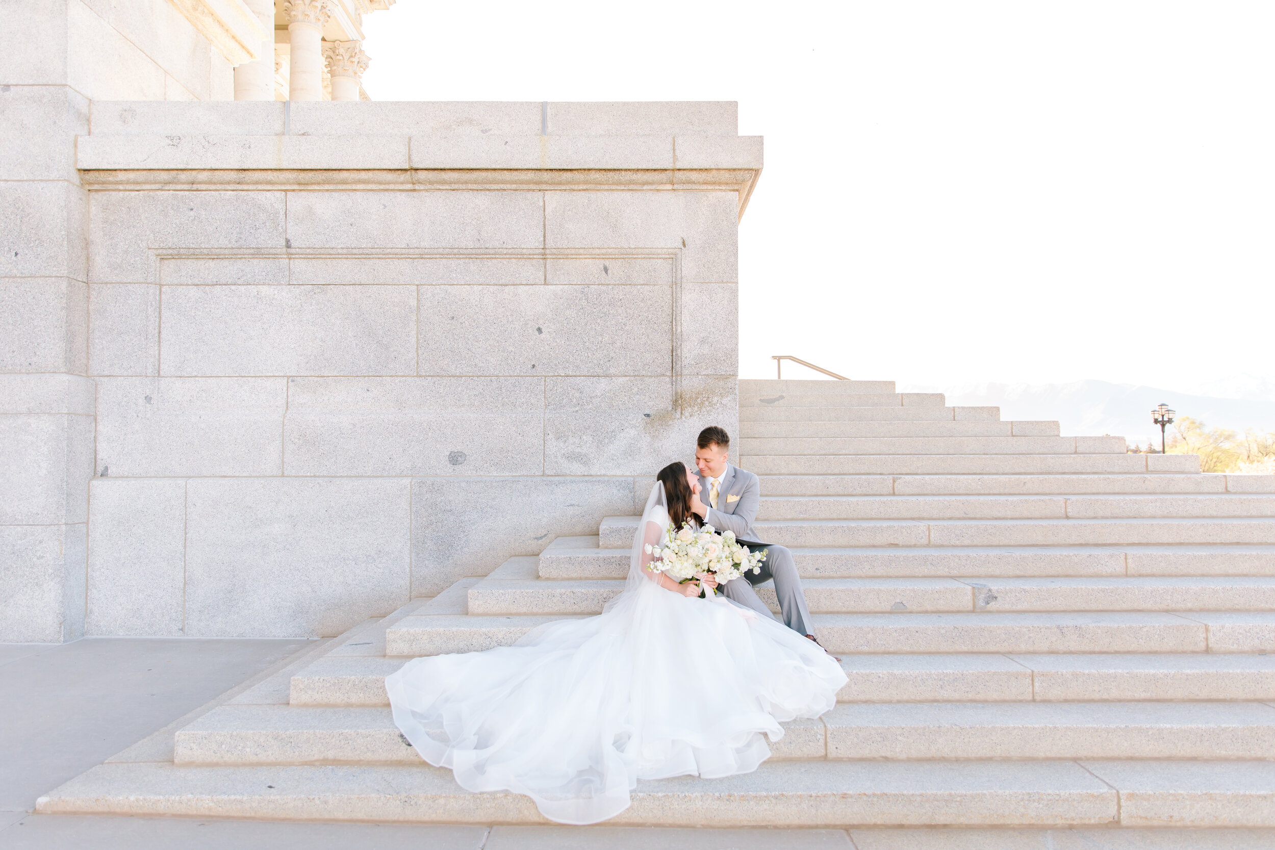 sitting on the steps couples pose inspiration looking into each others eyes couple goals formal wedding photo shoot session white granite steps salt lake city capital building bi wedding dress skirt wedding dress inspiration love the dress mens wedding tux inspiration wedding attire #formals #saltlakecity #capitalbuilding #lovebirds #couplegoals #bridal #weddinginspo #wedding #professional #photographer