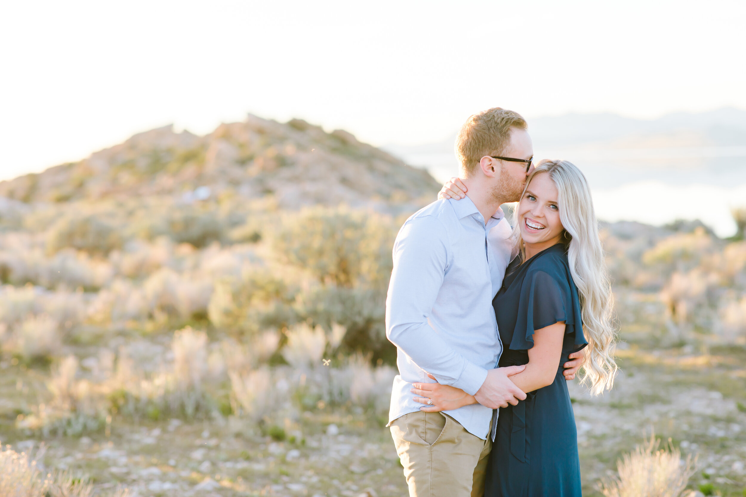 women's hairstyle inspiration soft curls hairstyle inspiration for engagement pictures couple holding each other kissing her head pose inspiration love on antelope island utah photo shoot location ideas free location inspiration in utah engagements #couplegoals #engagements #antelopeisland #couplekissing #engagementoutfitinspo #locationinspo #romantic #outside #engagementposes #engagementideas #weddingring