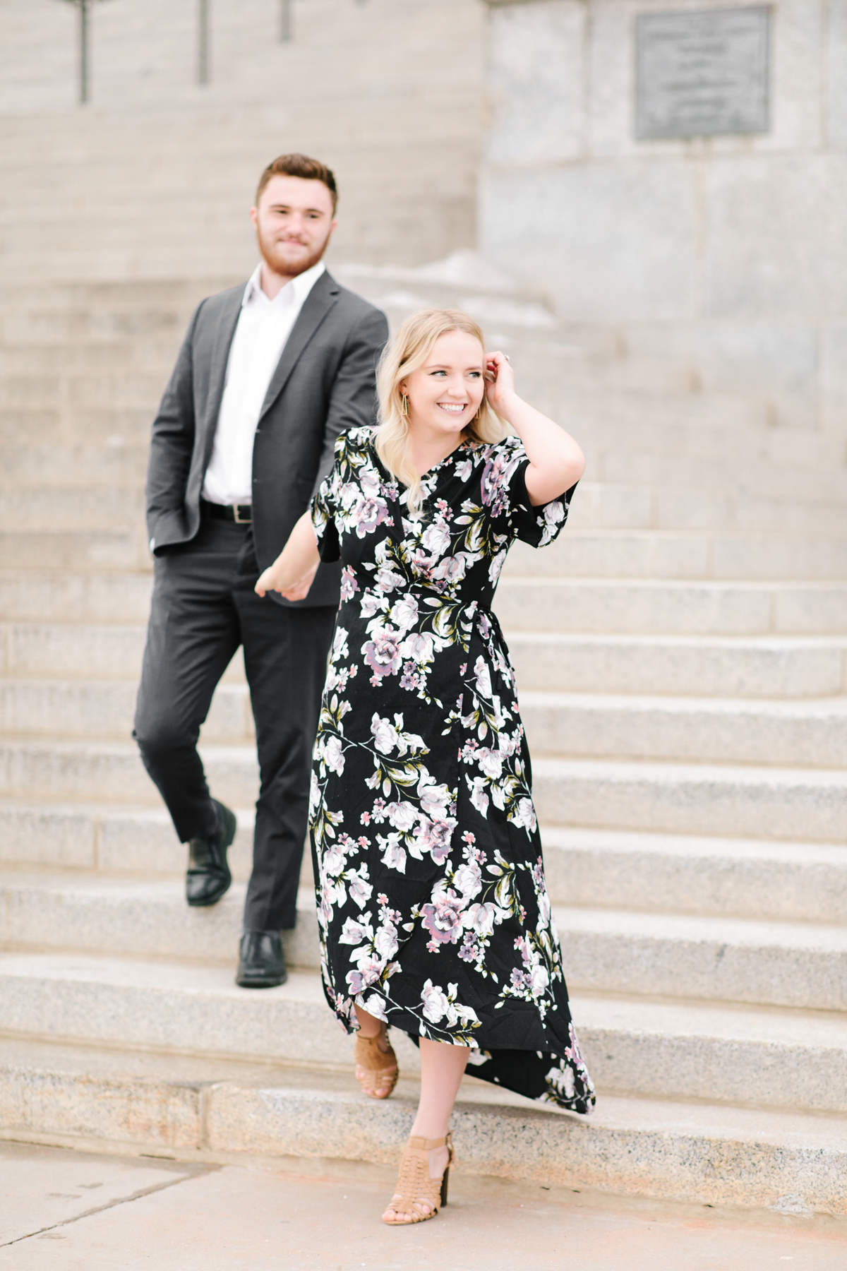 salt lake city capitol building descending staircase urban engagement session holding hands high low floral dress utah valley engagement photographer tucking hair behind ear #saltlakecitycapitolbuilding #engaged #utahvalleyengagementphotography #saltlakecityengagementphotographer #isaidyes #weddinginspo #engagementphotos #utah ##outfitinspo #fiance
