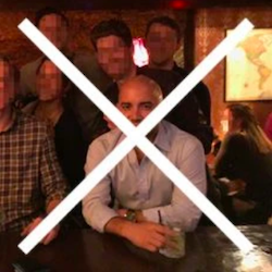 Why it's bad: At a bar, drink in hand, other people in the photo, too dark.