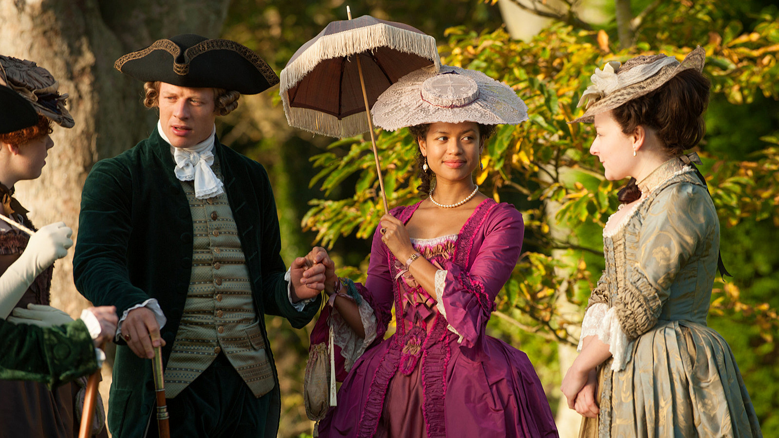 """Belle tells the story of Dido Elizabeth Belle, a mixed-race heiress, born in slavery but brought up in the world of the British aristocracy and is directed by Amma Asante who was inspired to make the film after seeing the portrait of 'Belle' and her white cousin, Lady Elizabeth Murray, seemingly painted as equals. Asante recalled """"This painting flipped tradition and everything the 18th century told us about portraiture. What I saw was an opportunity to tell a story that would combine art history and politics."""" While the film charts Belle's ascendancy to the aristocracy, it is also evident that Belle's material wealth and status created a facade of equality. In reality Belle's mixed-racial identity led to feelings of discontent and dislocation :- """"I am too high to eat with the servants, too low to join you at dinner,"""" Belle, played by Gugu Mbatha-Raw, tells Tom Wilkinson as the Earl of Mansfield. Belle was trapped between worlds, and not wholly welcome in either. The real-life Belle had a happy ending, was married, and was much loved by her family with the Earl of Mansfield leaving her a large portion of his will."""