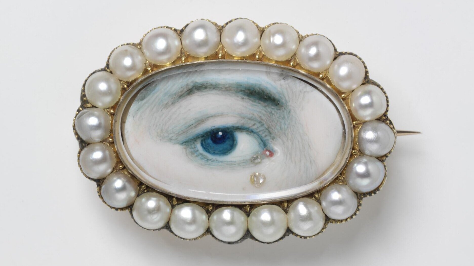 """What is a Lover's Eye?  Today we may send a selfie to our partner, but between the 1780s and 1820s, a Lover's Eye jewel was a secret way in which romantic relationships communicated. A painted miniature portrait of a person's eye, these tiny pieces were only centimeters in size and were exchanged between pining lovers. Due to their small stature, Lover's Eye jewellery could be both secretly or overtly worn, with the former for unknown courtships and the latter for public displays of affection.  The painted portrait was often crowned with gems and displayed in ovals, crescent moons or floral-like clusters to emphasise their inherent romantic nature. In many ways, these jewels were a literal jeweller's version of a synecdoche, with the eye communicating the whole being's intimate love and devotion. This one eye is the lustful watching gaze of their beloved, a """"look"""" that can only be understood between romantic partners.  In fact, eagle-eyed (pardon the pun) viewers may have noticed that this particular style of jewellery was actually shown in Bridgerton! Marina Thompson, the distant cousin of the Featherington family, is shown wearing a Lover's Eye pendant in her opening scenes, an instant sign that she has promised her heart to another suitor."""