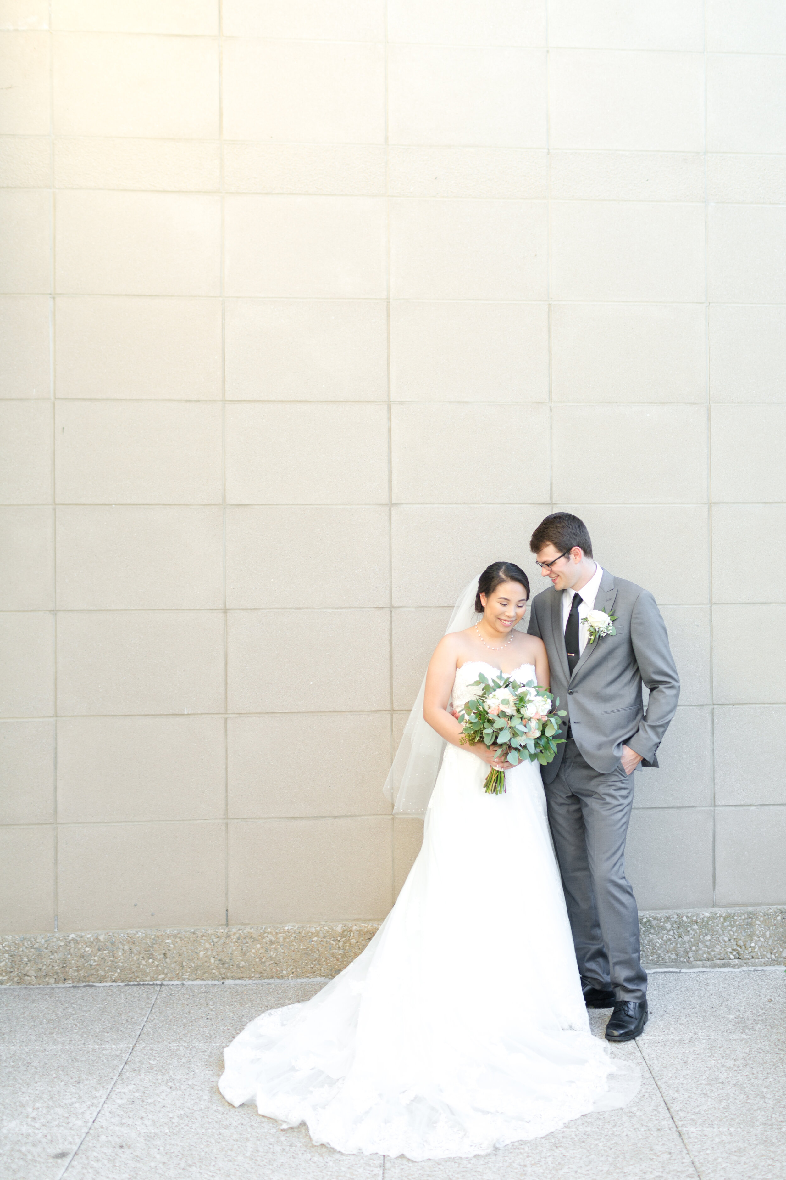 bride and groom in front of plain pale wall