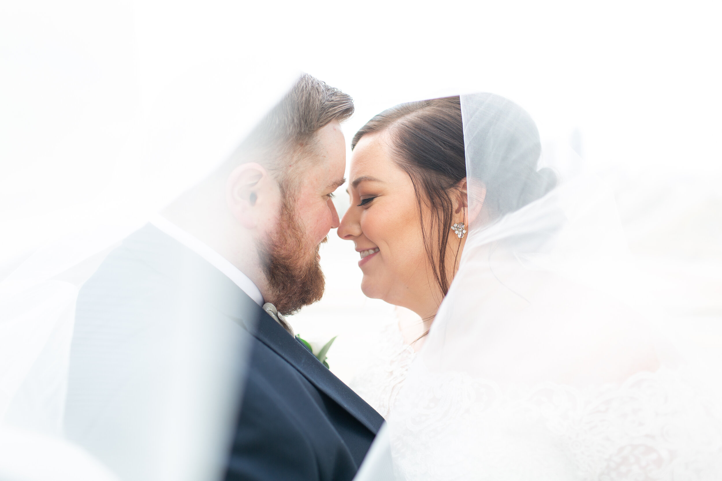 bride and groom under veil at first look
