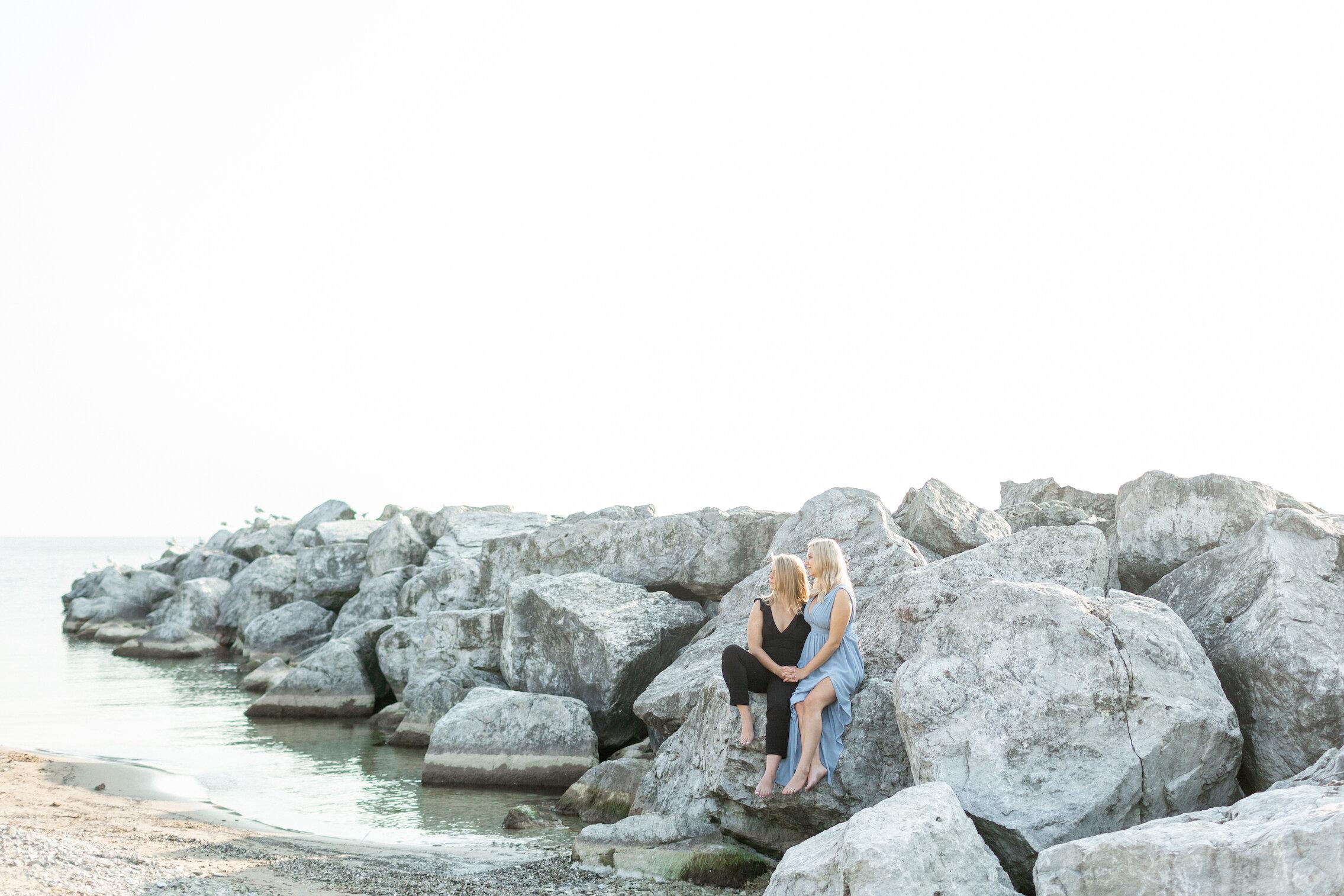 lesbian couple along rocky shore engagement session