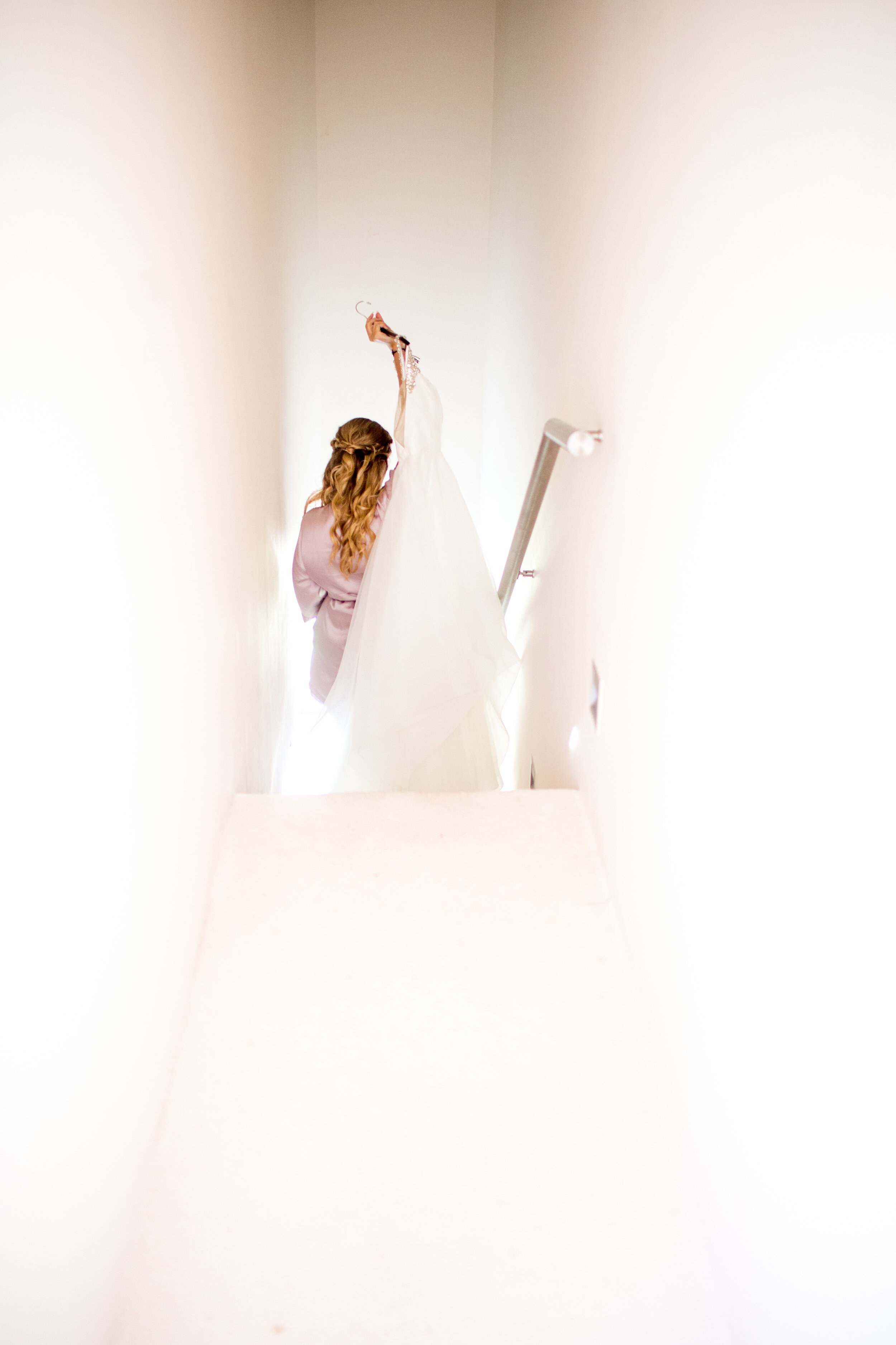 bride carrying dress down white corridor