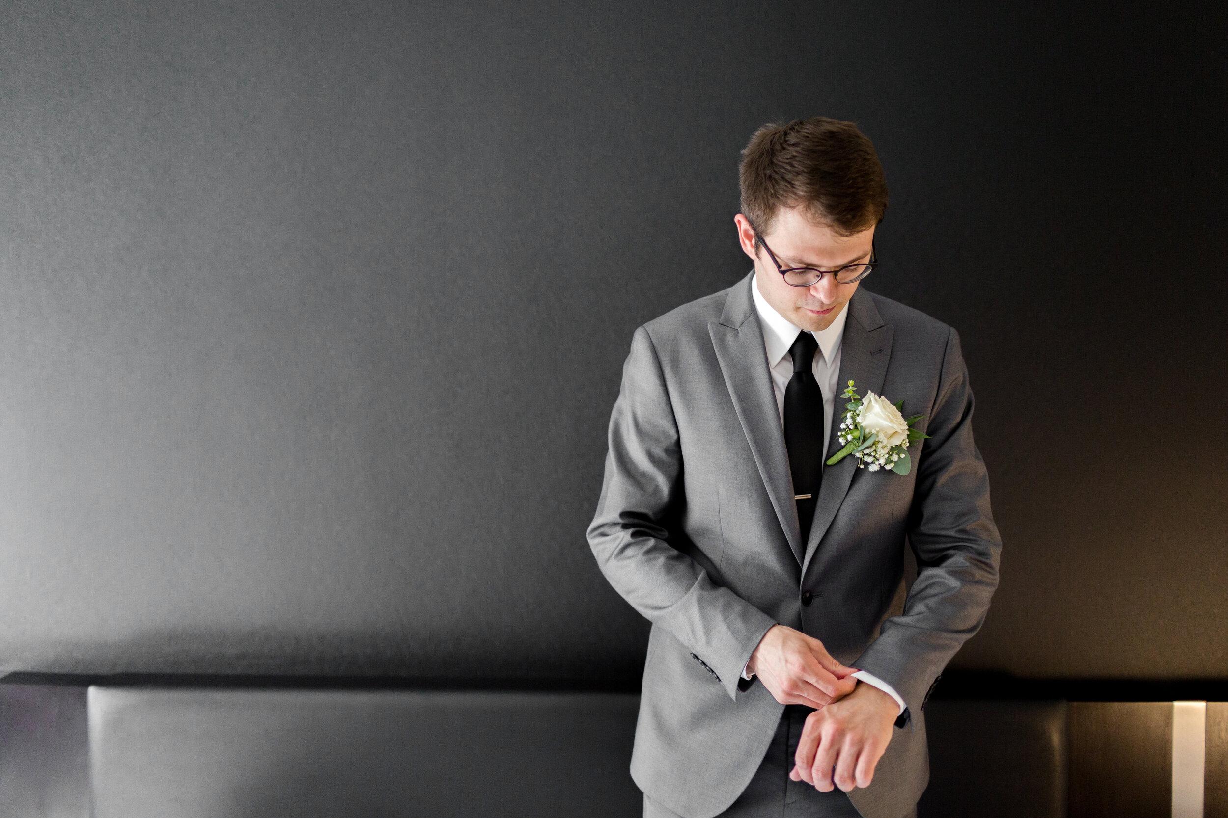 groom alone on black wall adjusting watch