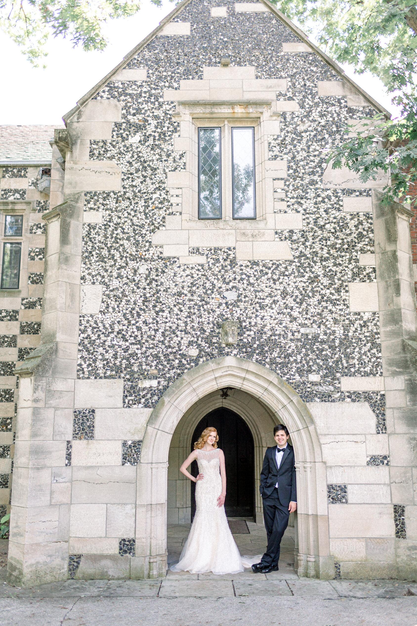 bride and groom in doorway arch of old building