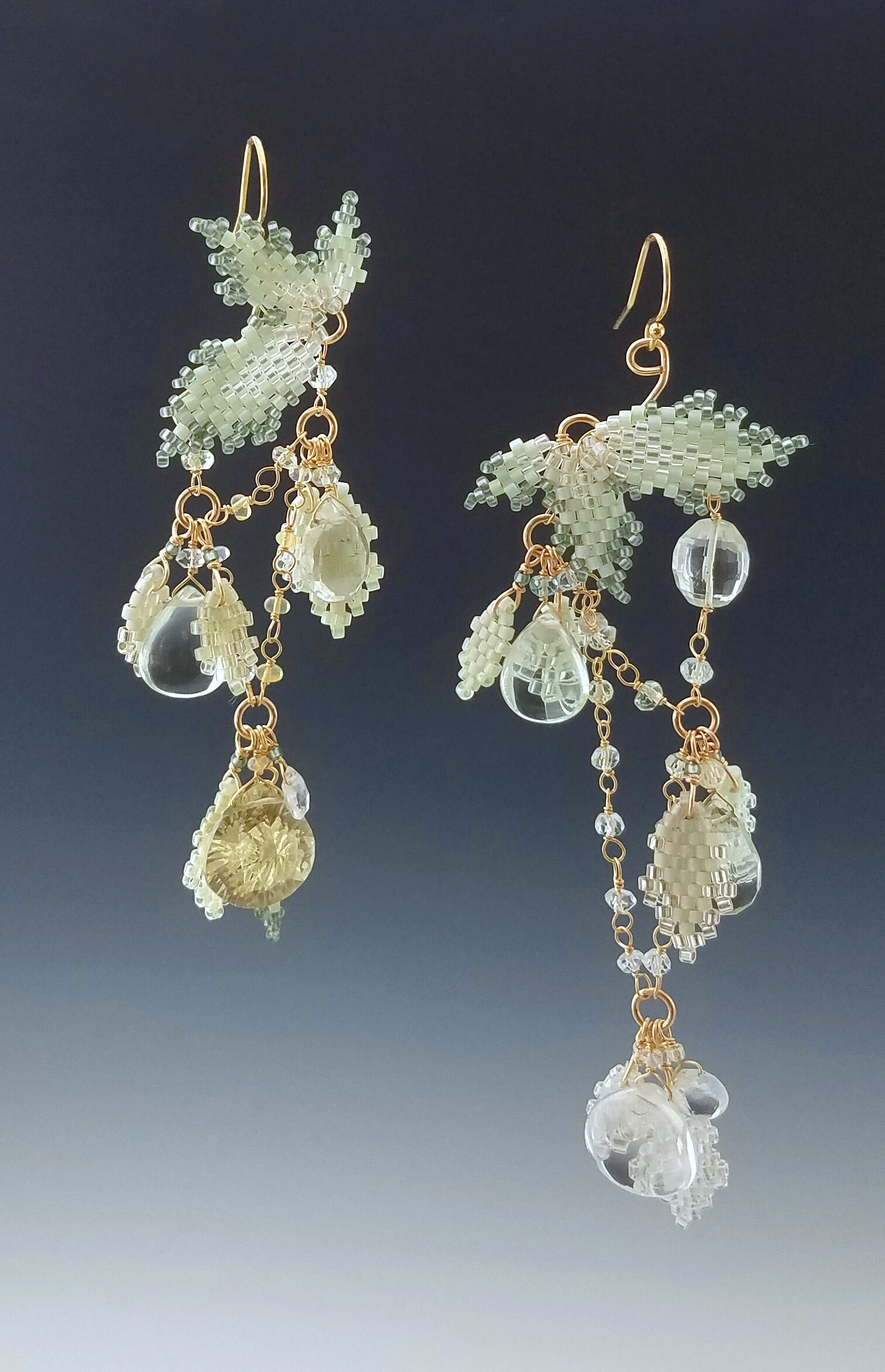 Hand-sewn gold earrings with beads and crystals.