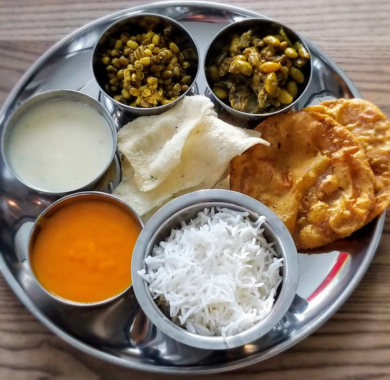 A thali is an assortment of small dishes served as a meal that differs from region to region. My family is from Gujarat, a state in west India known for its vegetarian dishes, so many of the recipes you find on here will tend to be the Gujarati version of Indian dishes.    The typical components of a Gujarati thali are rice, a bread item like puris, a few vegetable dishes, lentil gravies, and a sweet. Here we have the curried mung beans along with Basmati rice and puris, whose recipes you can find in the recipe box. We're going to work our way around the thali, learning about kadhi, the white gravy made from chickpeas;  papdi, a crunchy snack made from rice flour; papdi saak, another Indian vegetable dish.; and sweet and orange mango rus.