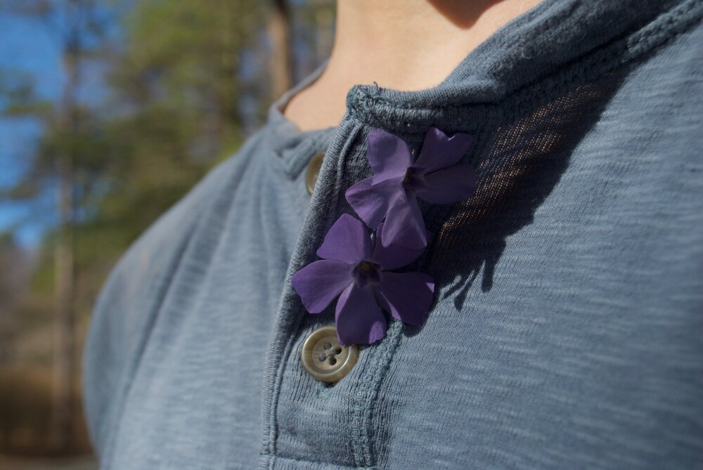 Two purple flowers tucked into the top two button holes of someone's shirt. Most of the image is occupied by the pale blue fabric of the shirt, with the flowers and buttons as the only details in focus. Tall trees blur in the sliver of background over the figure's shoulder. The image refers to a person by only showing a small aspect of them; a shoulder and part of the chest at collar bone level. There is a shadow of a chin. As in the other photos, we're denied access to more information through careful cropping. Tess is asking us to remain focused on the flowers, but the other details in her composition are intriguing too. Who put those flowers there and why?