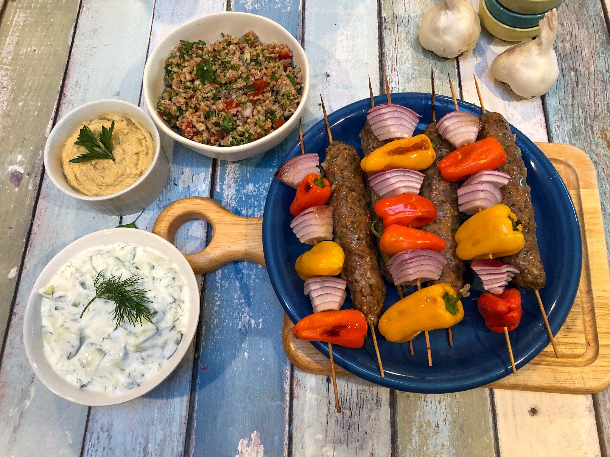 Mediterranean meal with Fat-Free Tzatziki, Hummus, Tabbouleh, an Kebabs.
