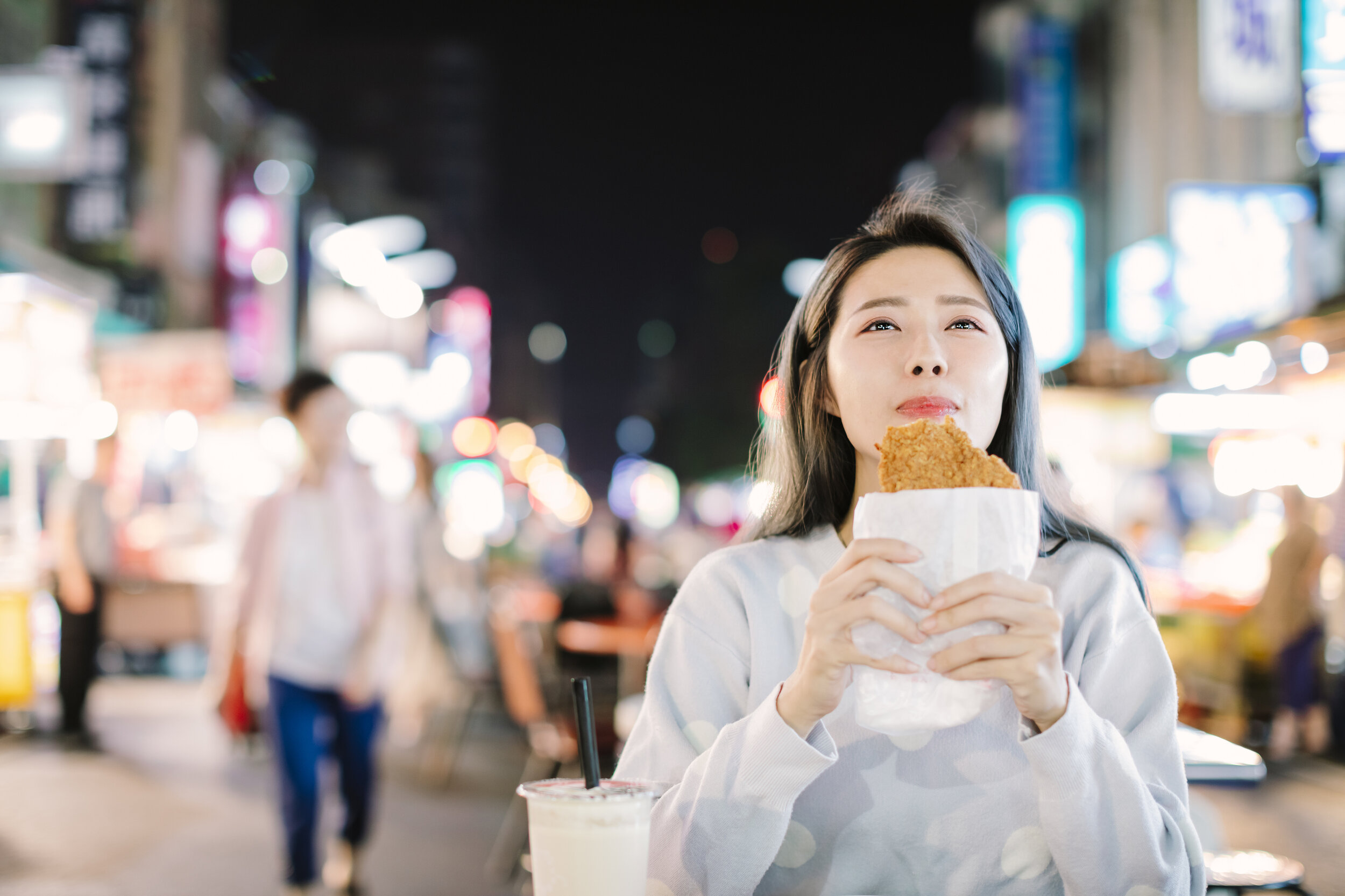 Woman eating Chicken Fillet street food in Taipei.