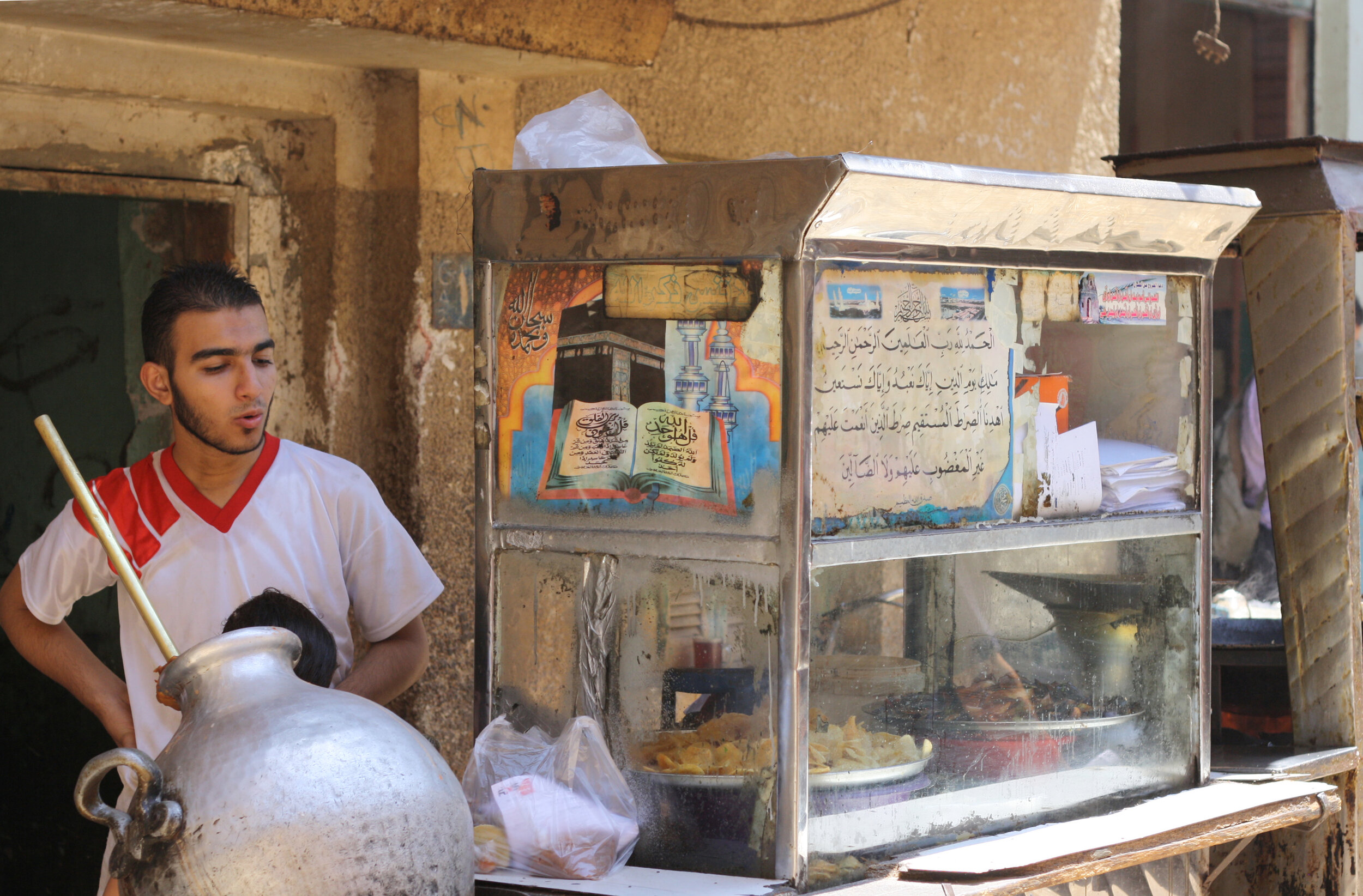 The national dish, ful, served as Egyptian street food from a large silver pot.