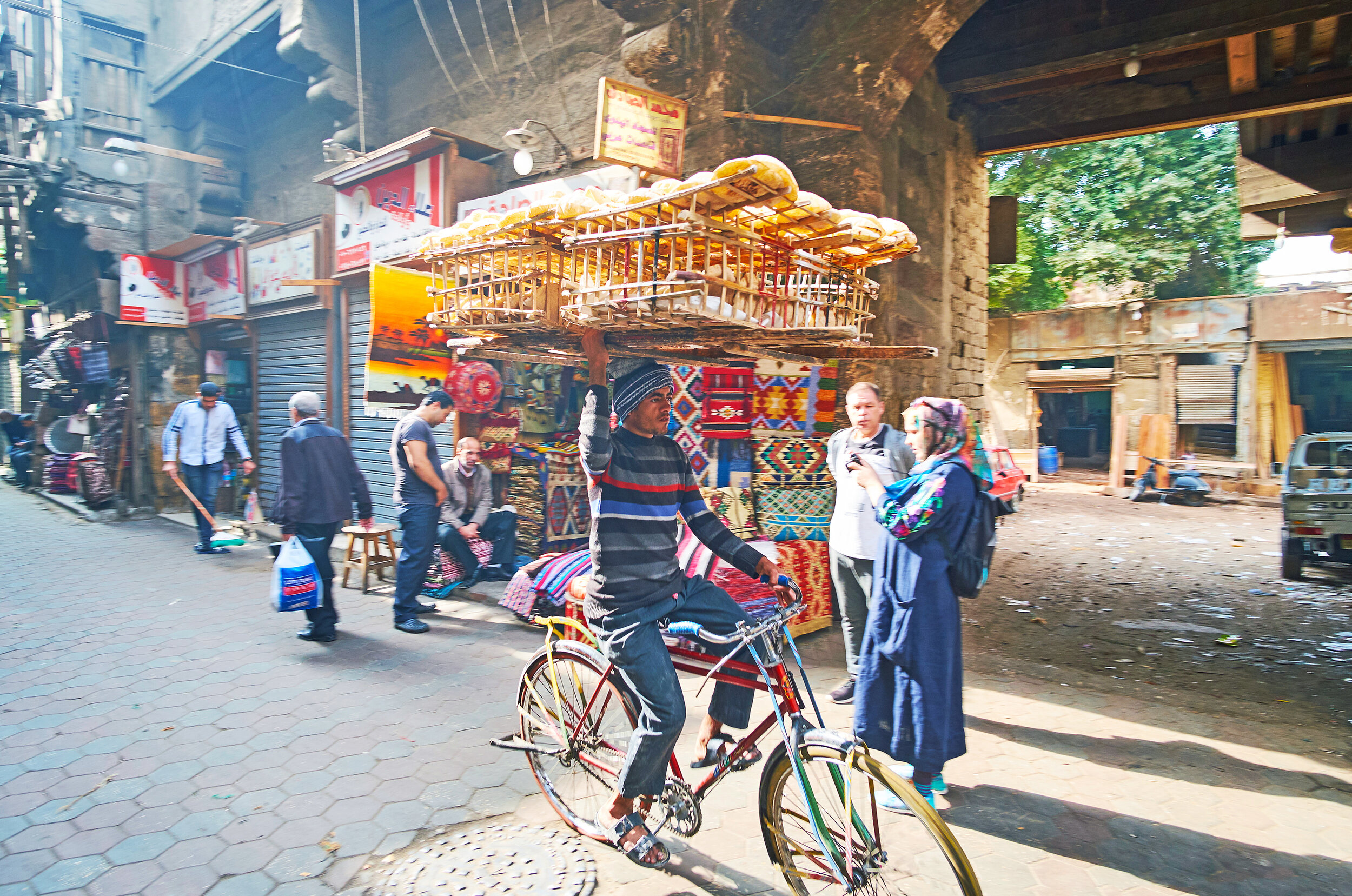Egyptian street food vendor riding a bike in Cairo.