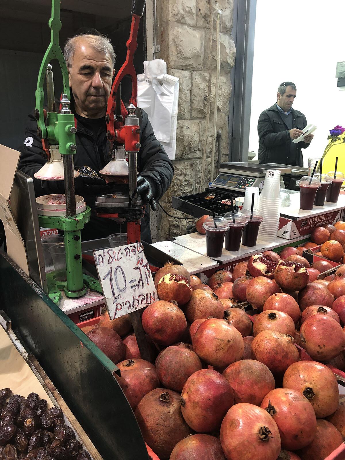 Street vendor selling refreshing Israeli drinks like pomegranate juice.