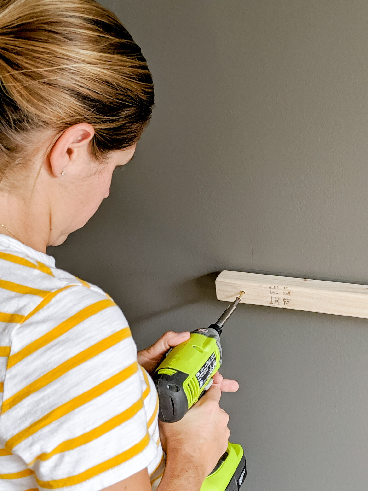 Me, screwing the ledger board into the wall for our homework station surface. Not pictured: my husband behind me cringing because he wants to do it himself.